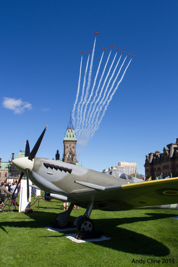 "The CT-114 Tutors of the Canadian Forces Snowbirds fly the ""Missing Man"" formation over Parliament Hill during the ceremony held there on September 20, 2015, to mark the 75th anniversary of the Battle of Britain. In the foreground is a replica of a Second World War Supermarine Spitfire, one of the principle fighter aircraft flown by the allied forces during the Battle of Britain. PHOTO: © Andy Cline, used with permission"