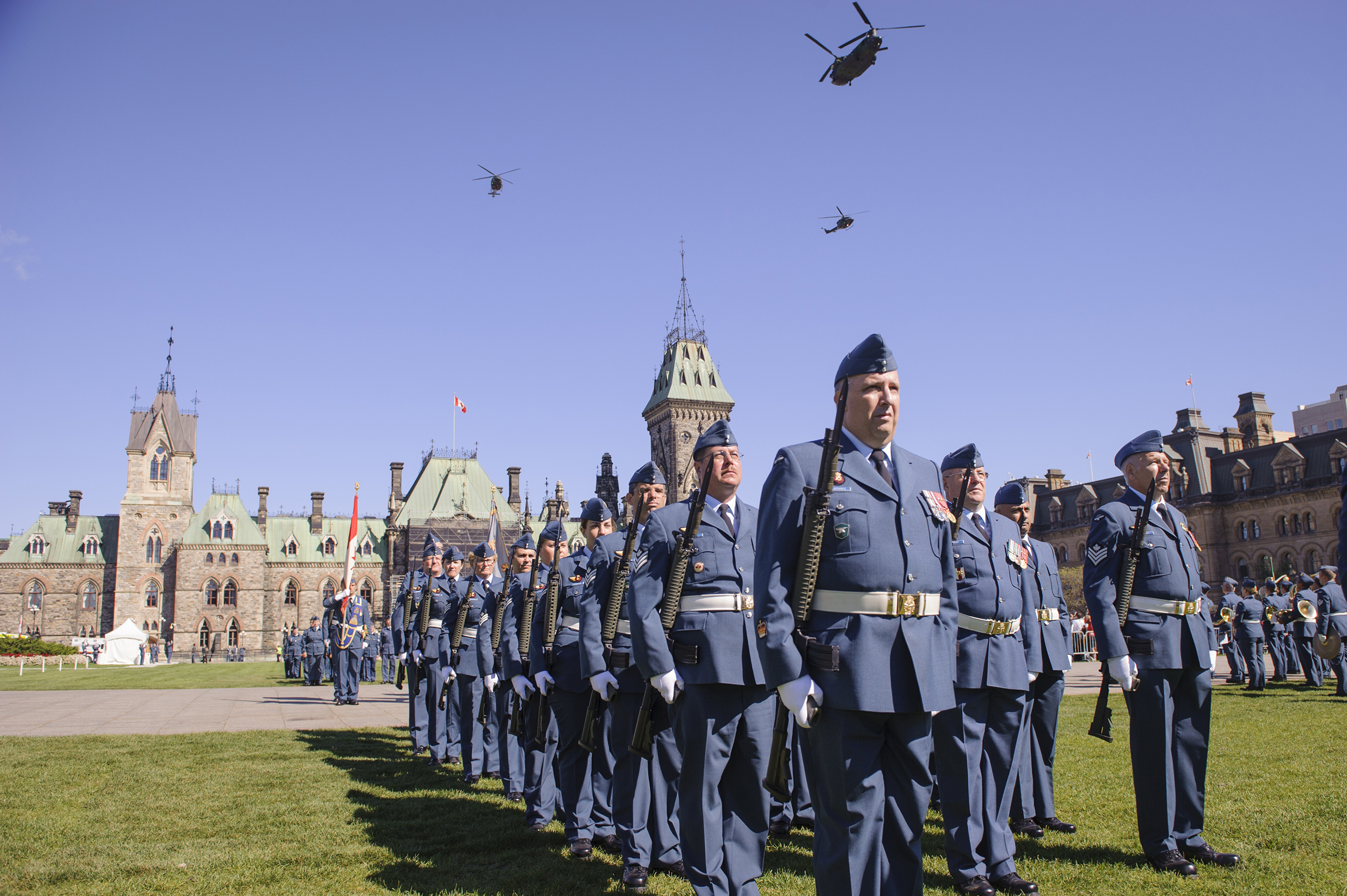 Members of the Royal Canadian Air Force on parade during the national Battle of Britain ceremony on Parliament Hill, September 20, 2015, as a CH-147F Chinook helicopter and two CH-146 Griffon helicopters fly overhead. PHOTO: Master Corporal Daniel Merrell