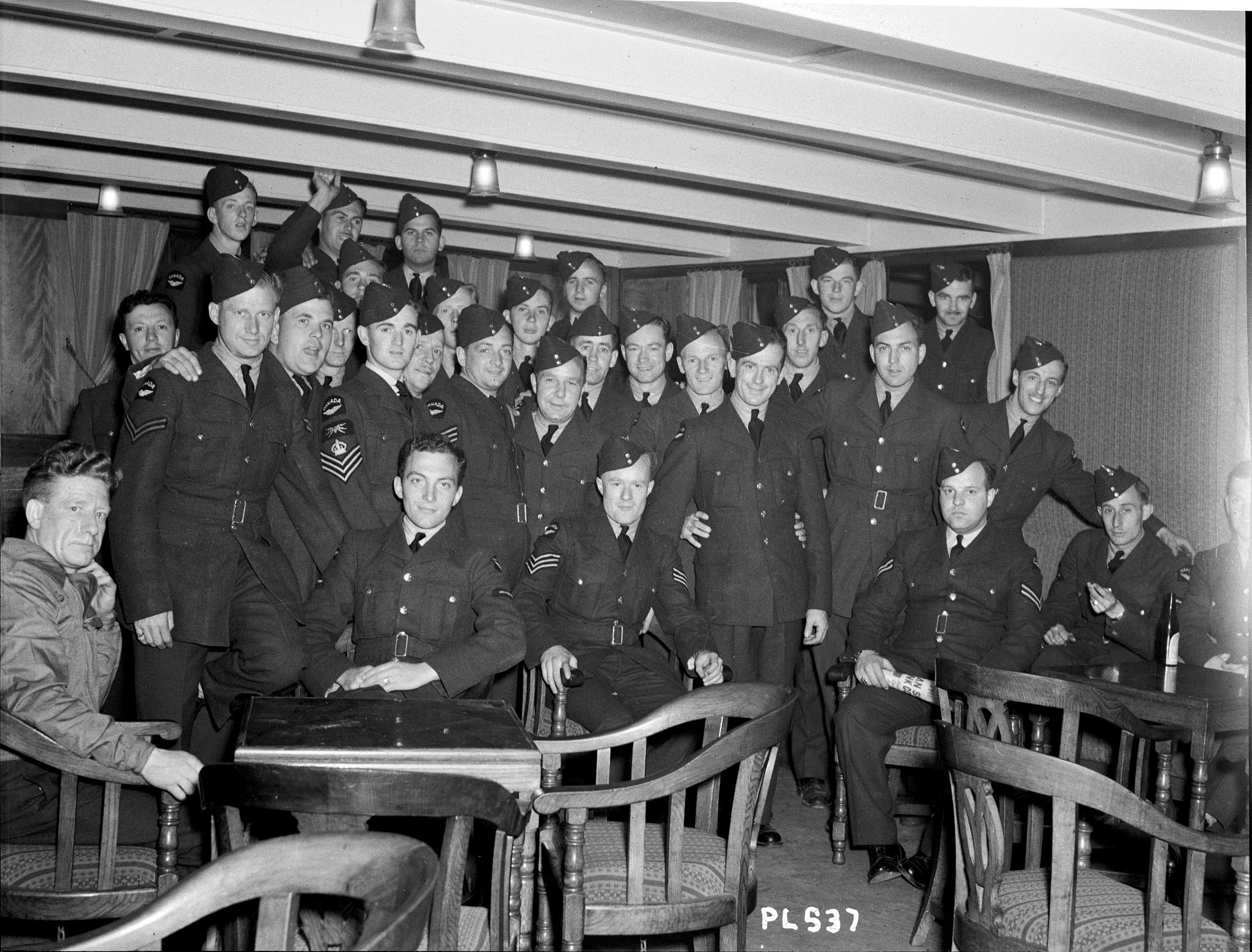 Airmen of of the RCAF's No. 1 (Fighter) Squadron sit for a photograph on board ship on June 8, 1940, before departing for Europe on active service. Soon after their arrival in Great Britain, many, if not all, would undoubtedly be in the thick of things during the Battle of Britain. PHOTO: DND Archives, PL-537