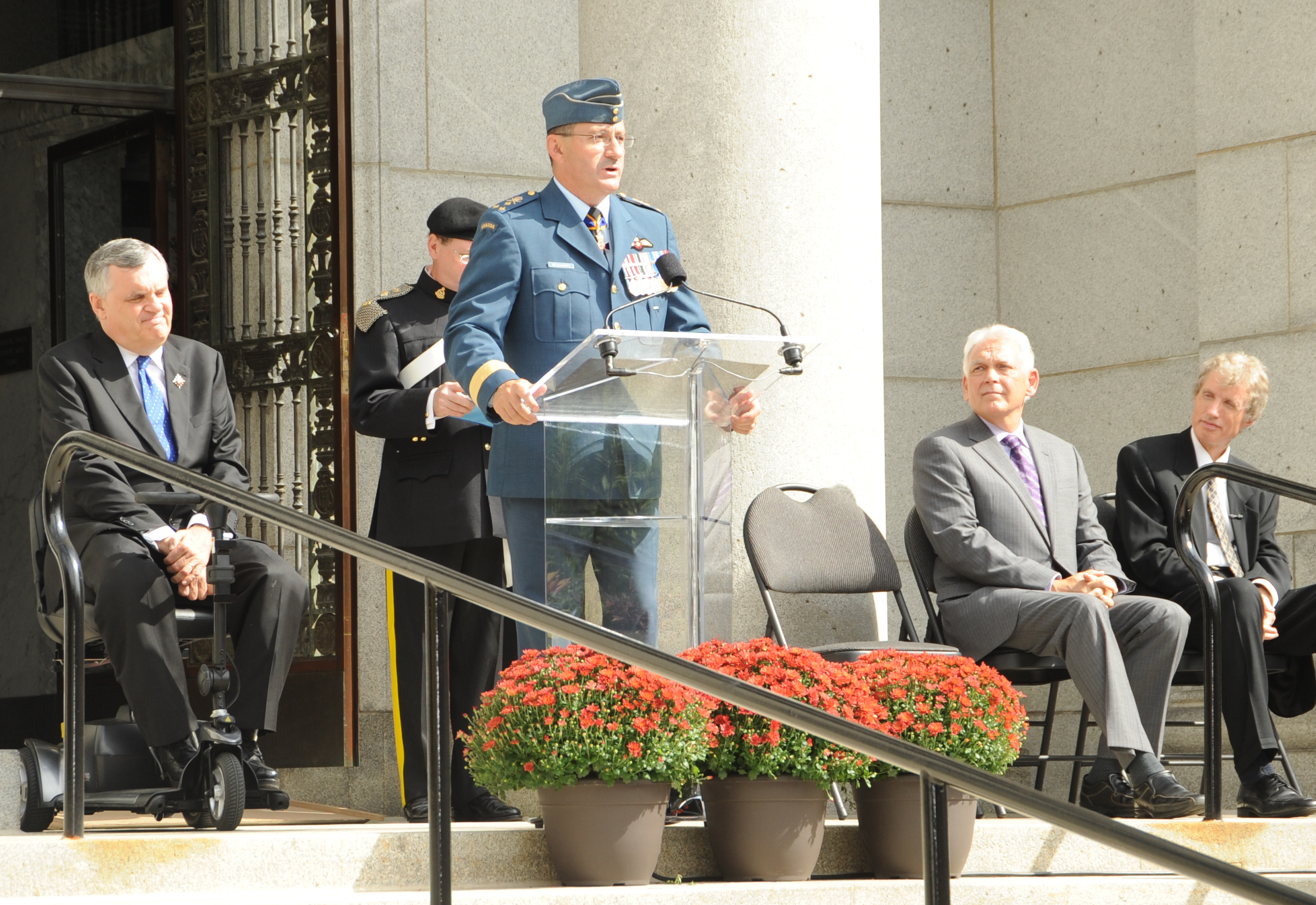 Lieutenant-General André Deschamps, commander of the RCAF, addresses the crowd prior to the dedication of the monument in honour of Wing Commander Barker.   To his right is Ontario's Lieutenant-Governor David Onley, behind him is John Wright, seated are Wayne Ralph and Ian Mackenzie (far right). PHOTO:  Master Corporal Clesse Howse