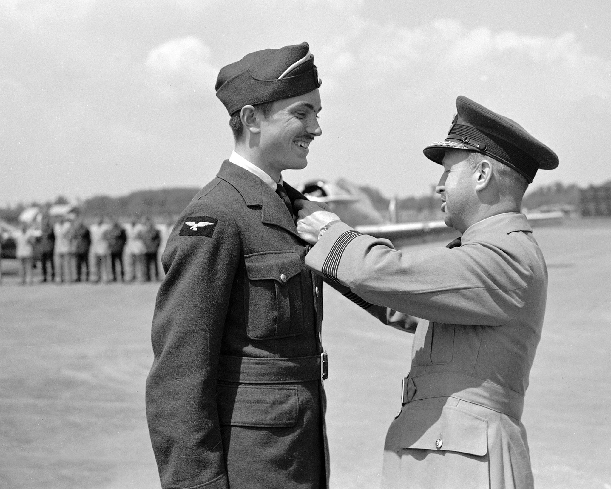 "Group Captain W.A. Curtis (right) presents wings to Pilot Officer John Gillespie Magee, author of ""High Flight"", in June 1941, at RCAF Station Uplands, near Ottawa, Ontario."