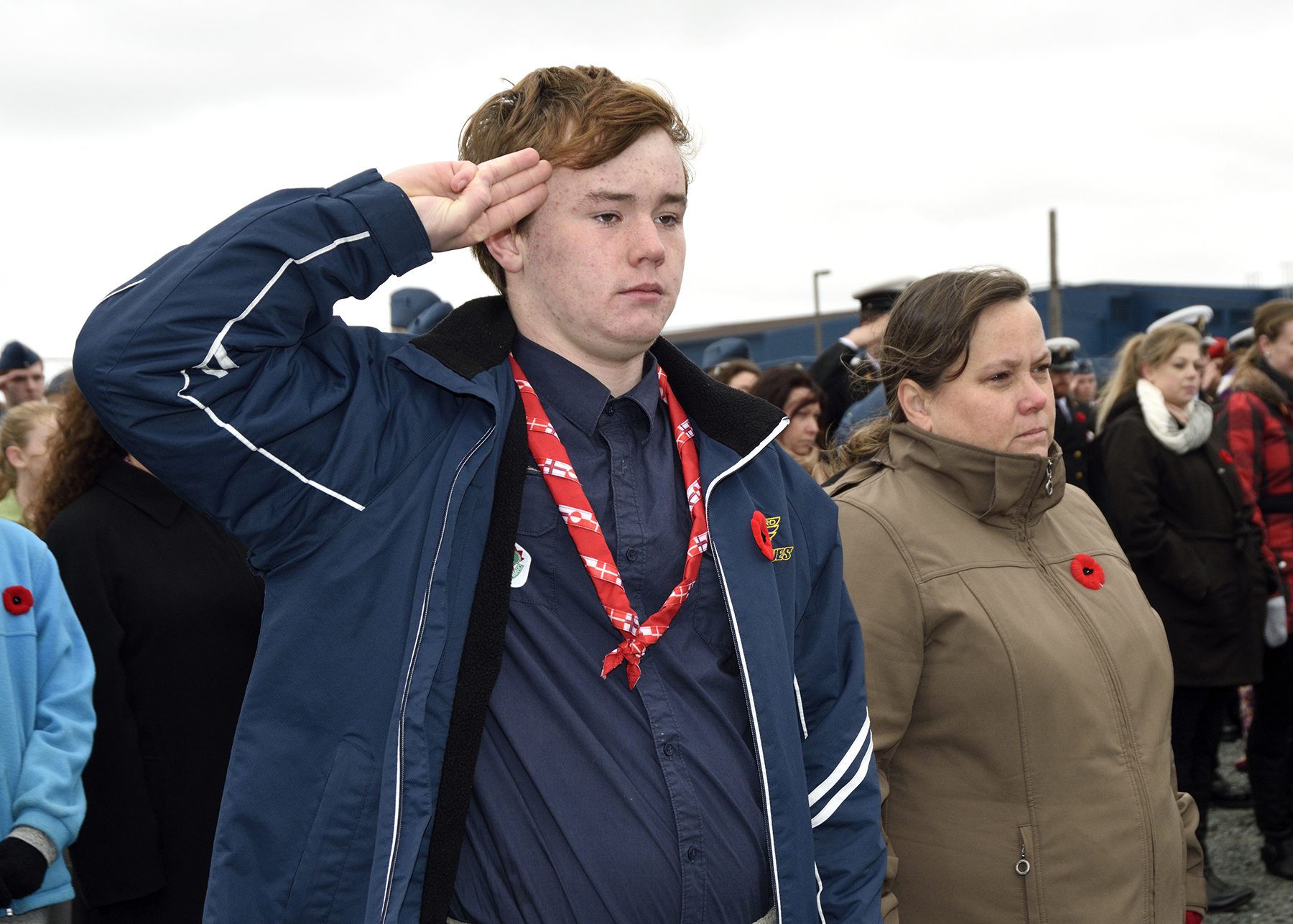 "Ian VanOosten, a member of Scouts Canada, 1st River Lake, Nova Scotia, salutes during the sounding of ""Last Post"" during the Remembrance Day ceremony at the 12 Wing Shearwater Afghanistan Memorial, at 12 Wing Shearwater, Nova Scotia. PHOTO: Corporal Jennifer Chiasson"