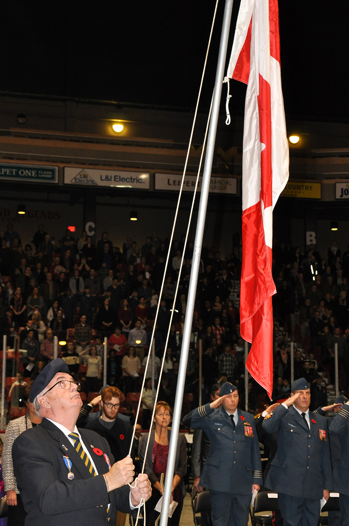 Canadian veteran Bob O'Riley raises the flag and Royal Canadian Air Force members salute following the sounding of Reveille during the 15 Wing Remembrance Day ceremony on November 11, 2015, at Moose Jaw, Saskatchewan's Mosaic Place. PHOTO: Lieutenant Jenn Halliwell