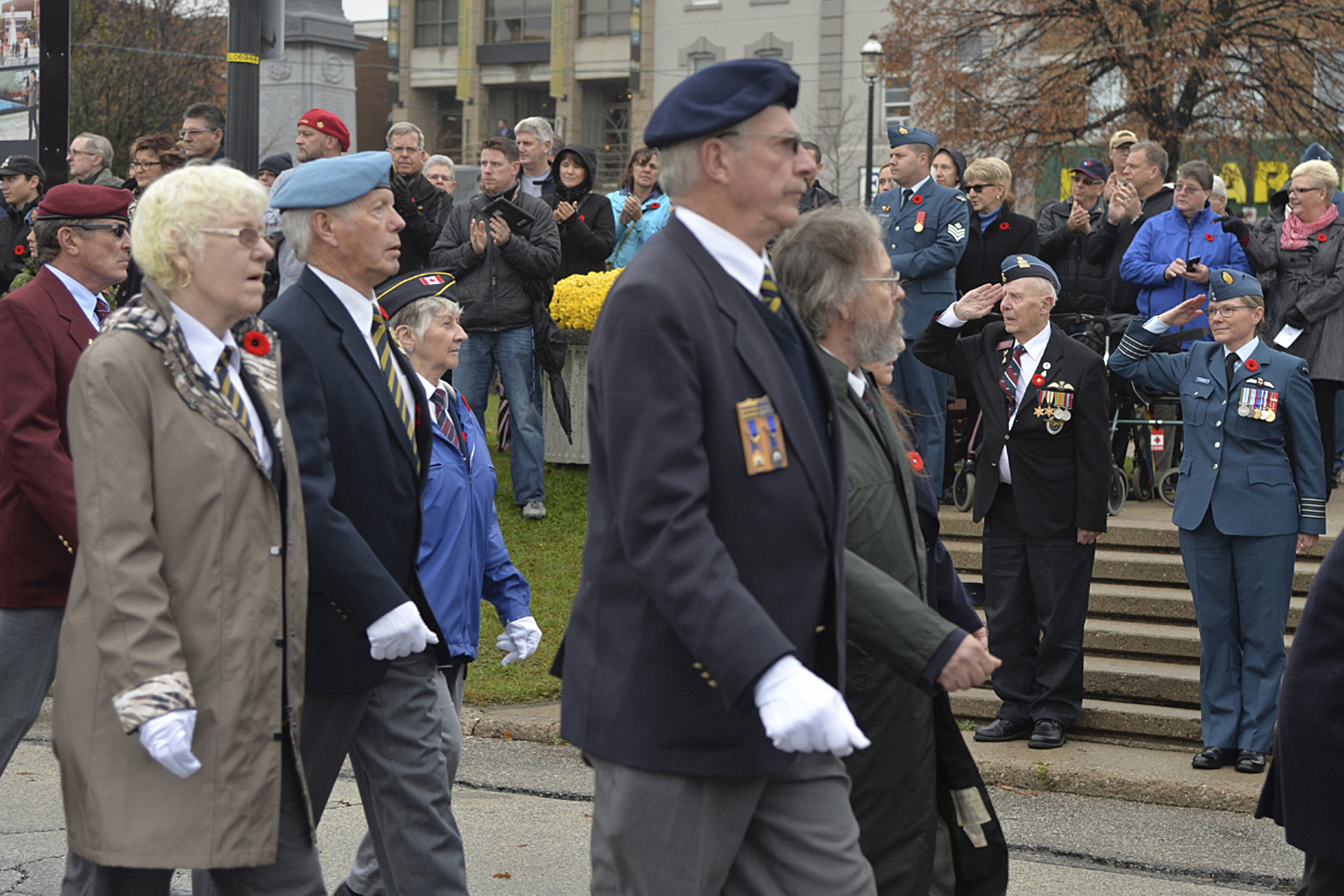 Members of the veterans contingent receive salutes from 16 Wing Borden, Ontario, commander Colonel Yve Thomson (right) and veteran Tom Carney, and applause from those attending the November 11, 2015, Remembrance Day ceremony held in Barrie, Ontario. PHOTO: Master Corporal Miranda Langguth
