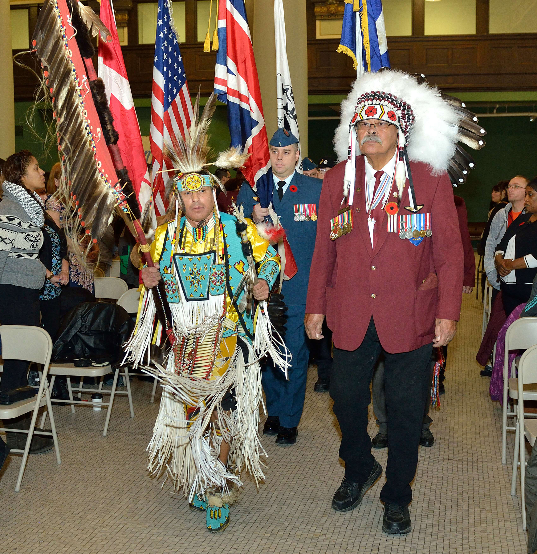 During the Aboriginal Veteran's Day Ceremony held on November 6, 2015, at the Centre for Aboriginal Human Resource Development in Winnipeg, Manitoba, the grand entry of the Eagle Staff is led by dancer Lauren Stevenson and George Anderson in the eagle feather headdress, followed by 17 Wing Winnipeg's Sergeant Matthew Keddy. The wing's Defence Aboriginal Advisory Group and the wing command team of Colonel Andy Cook and wing Chief Warrant Officer Mike Robertson participated in the ceremony. PHOTO: Sergeant Bill McLeod