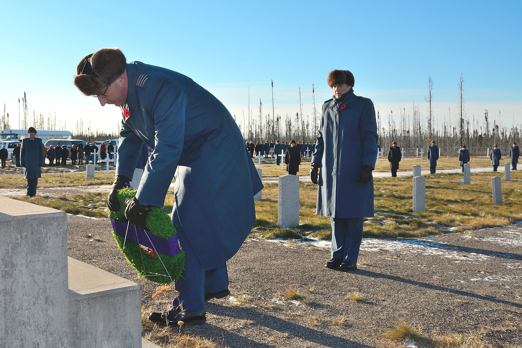 In the Commonwealth Cemetery at 5 Wing Goose Bay, Newfoundland and Labrador, Master Warrant Officer Lori White watches as Lieutenant-Colonel Luc Sabourin, commander of 5 Wing, places a wreath in tribute to the fallen during the November 11, 2015, Remembrance Day ceremony. PHOTO: Master Corporal Krista Blizzard