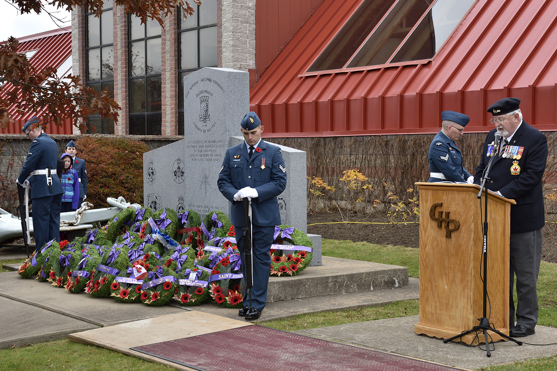 While Royal Canadian Air Force sentries stand vigil at the cenotaph, Comrade Terry Pond, 1st vice president and poppy chair of Royal Canadian Legion Centennial Branch #160, calls the names of wreath bearers during the November 11, 2015, Remembrance Day ceremony held at Cole Harbour Place in Dartmouth, Nova Scotia. PHOTO: Corporal Anthony Laviolette