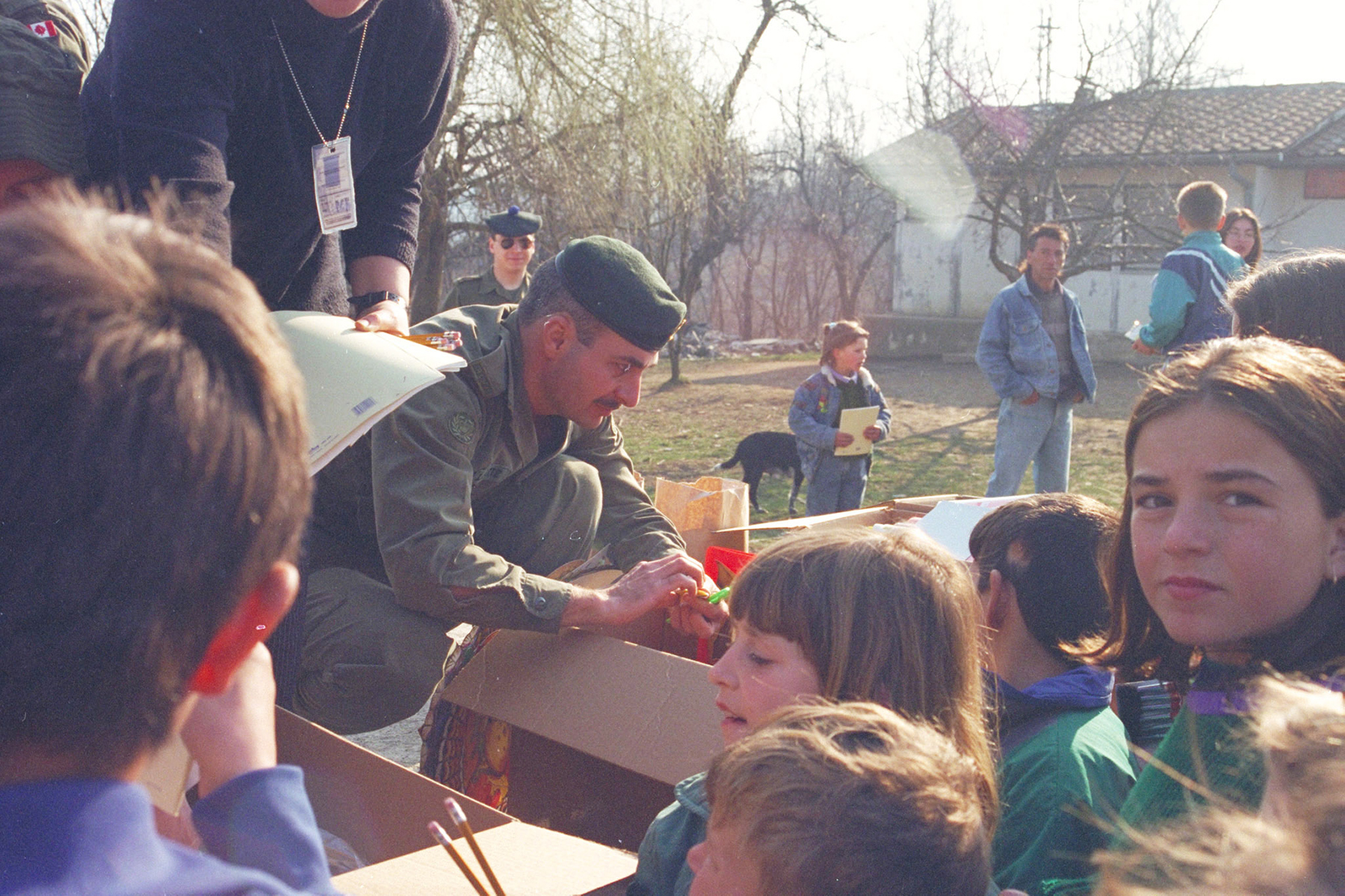 Christmas comes early for students of the Rajnovac School in Rajnovac, Bosnia (now Kosovo) as Canadian Forces members help students open and look through boxes of books donated by the soldiers. PHOTO: Sergeant Lavallee