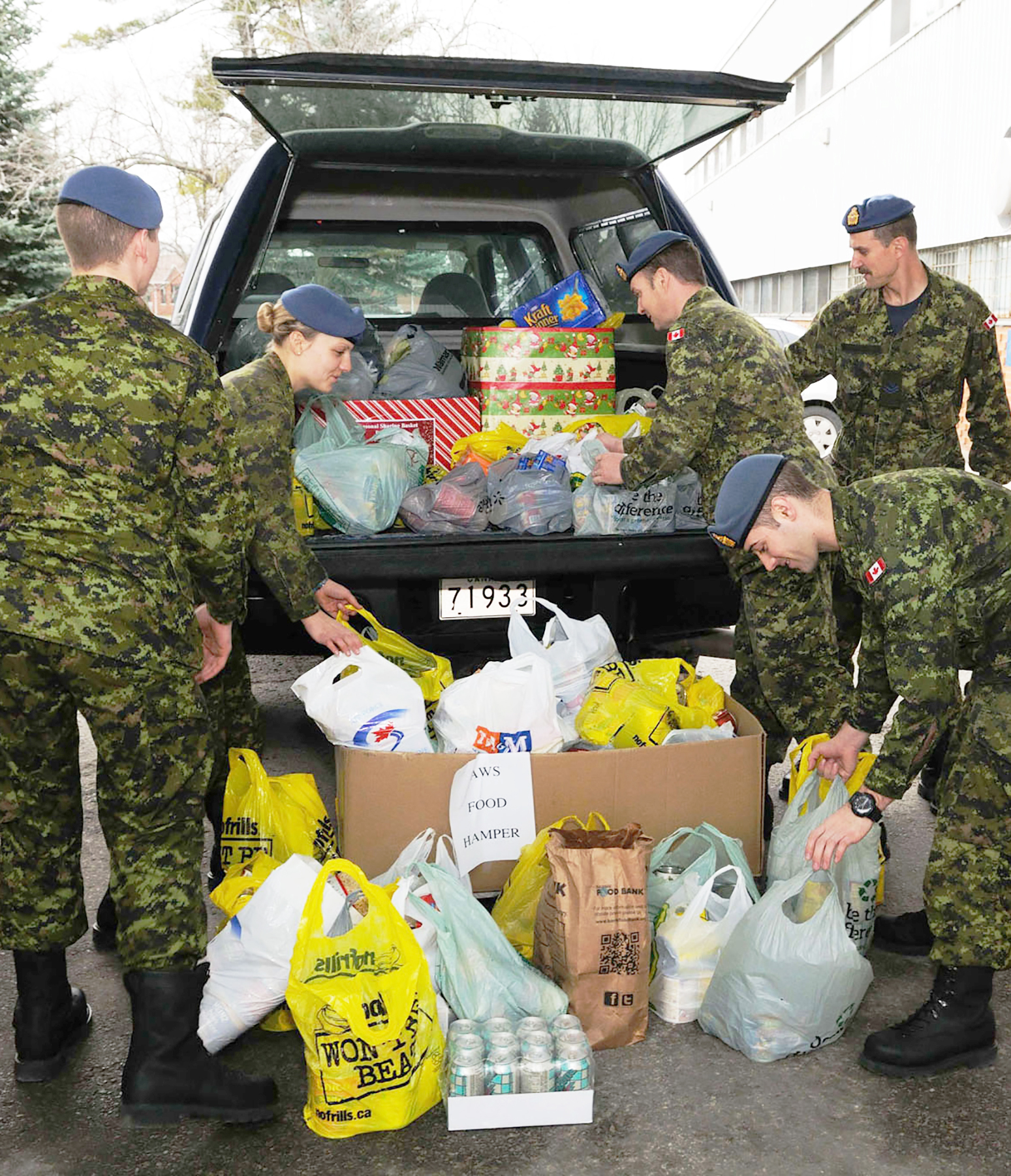 Private Spencer Hollerman (left), Private Amanda Dingman, Sergeant Howie Honka, Master Corporal Darrel Kresky and Private Doug Trinnear load more than 363 kilograms of non-perishable food collected for the Seasonal Sharing Basket by personnel of the Canadian Forces School of Aerospace Technology and Engineering, a lodger unit of 16 Wing Borden, Ontario, on December 3, 2012. The Seasonal Sharing Basket is a campaign providing assistance to Defence Team families in need of additional support over the stressful Christmas/Holiday period. PHOTO: Sergeant Kev Parle