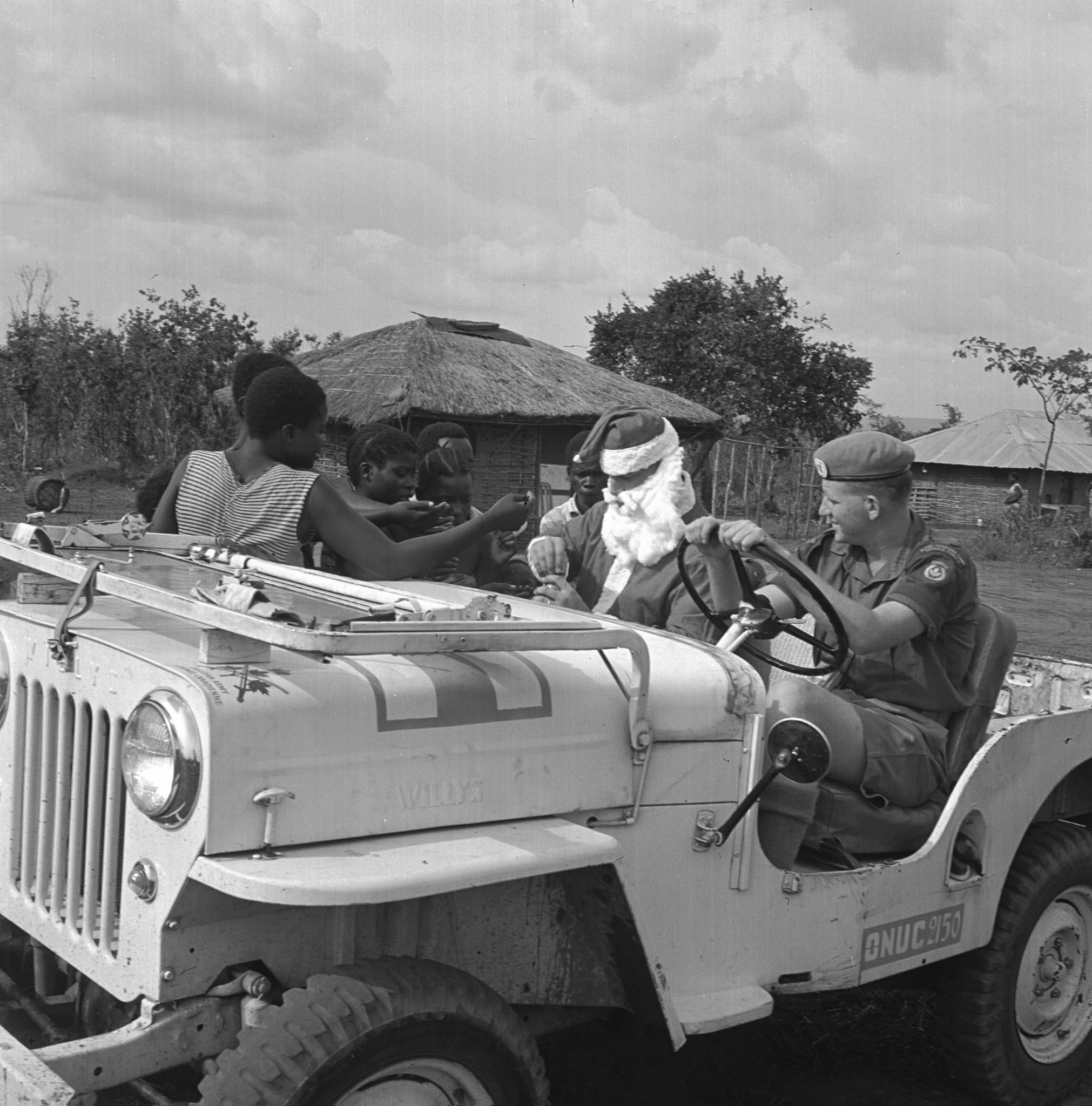 Driven by Private Kenneth Goble, Santa, a.k.a. Corporal Maurice LeClair, arrives by jeep in one of the villages close to Leopoldville, Congo. The members of No. 57 Canadian Signals Unit, part of the United Nations force in the Congo, visited the village to give candies and other gifts to the children in December 1963. PHOTO: DND Archives