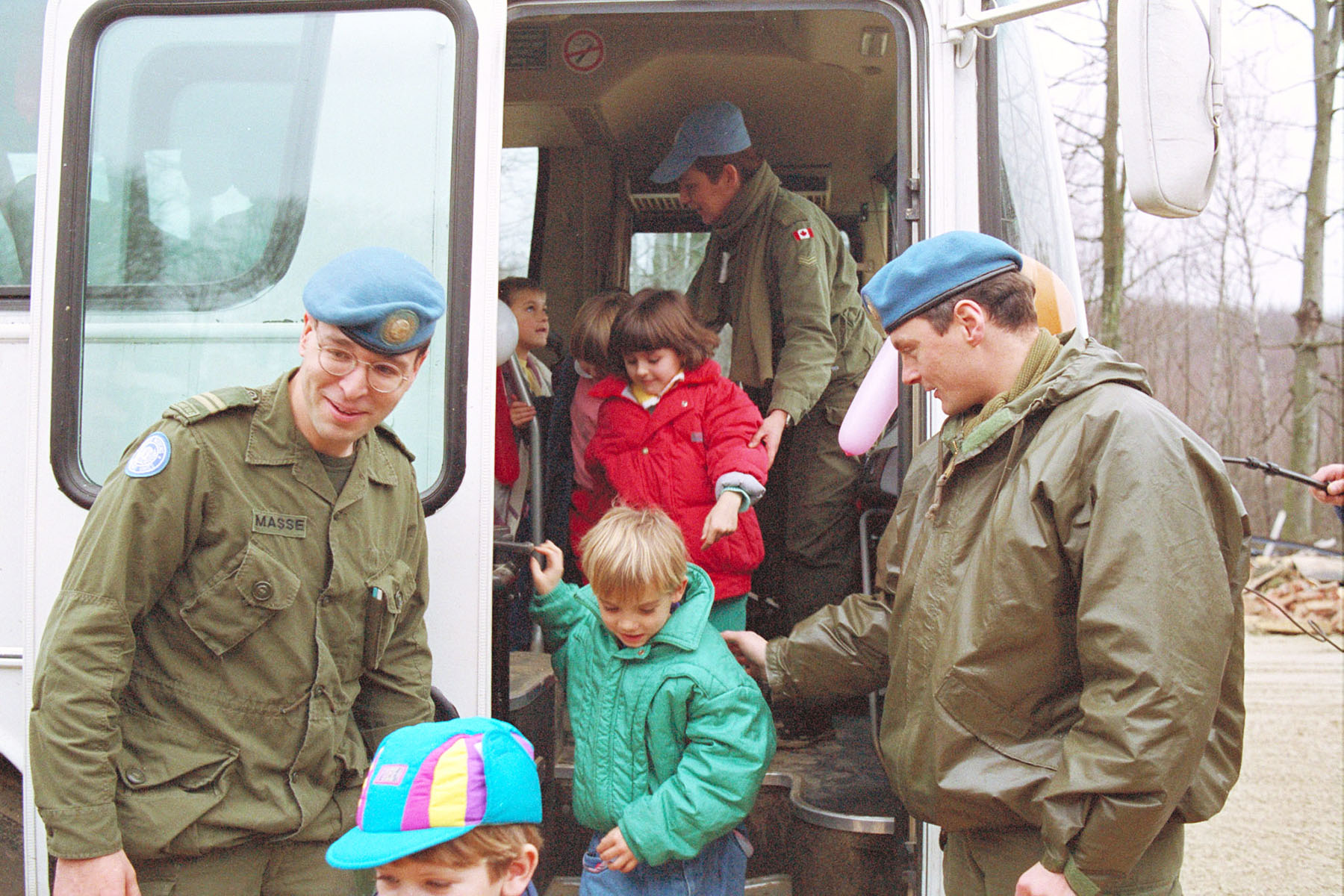 In Daruvar, Croatia, in 1992, Captain Phillipe Masse (left) and Captain Richard Nantel assist schoolchildren from the bus that has carried them to the Children's Christmas Party at Camp Polom. The children were hosted by personnel who were on peacekeeping duty in Croatia. PHOTO: Sergeant R. Thompson