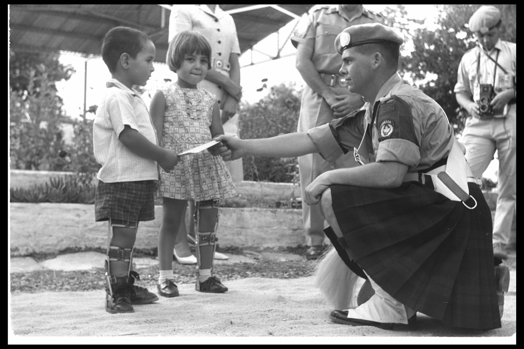 In late autumn 1966, Private J.M. McNeil presents a cheque for $1,500 to children at the Greekturk Cypriot Kyrenia Sick Childrens Hospital in Cyprus. PHOTO: DND Archives