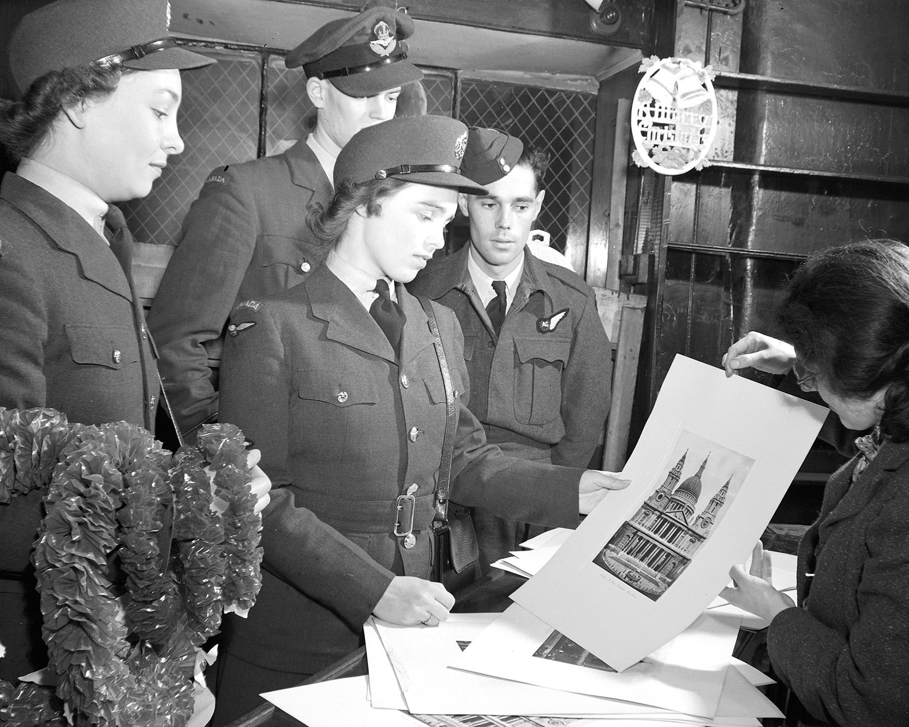 "On October 16, 1943, in the original ""Old Curiosity Shop"" of Charles Dickens' novel, Leading Aircraftwoman Shirley Stewart (left) (La Riviere, Manitoba) and Leading Aircraftwoman Geraldine Reid (Minnedosa, Manitoba), members of the Royal Canadian Air Force Women's Division Overseas, and Royal Canadian Air Force members Pilot Officer Thomas Teasdale (centre) (Edmonton, Alberta) and Warrant Officer Jack Lineham (Calgary, Alberta) select gifts to send back home for Christmas. PHOTO: DND Archives"