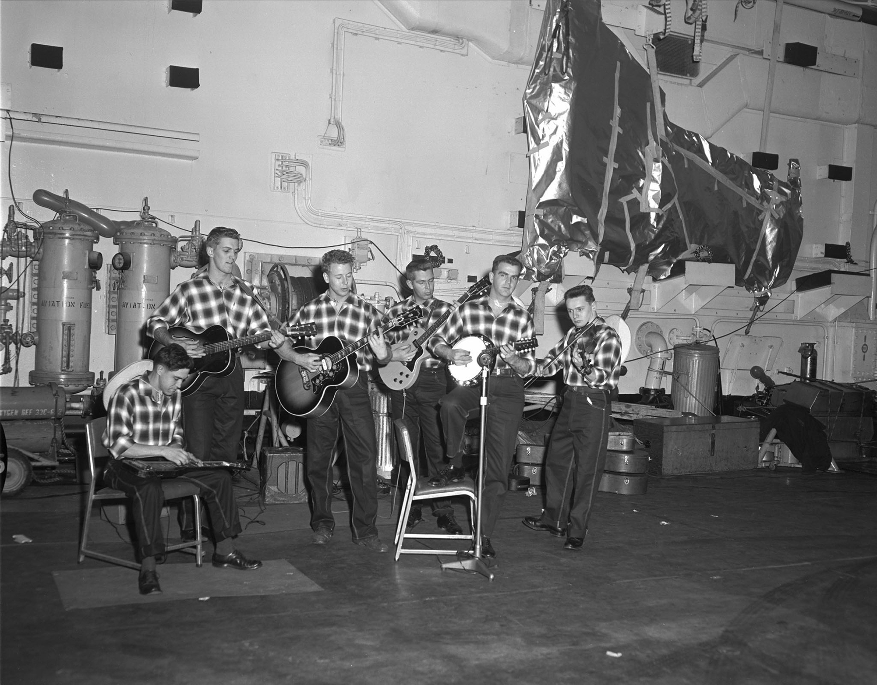 The Bonaventure Drifters, all crew members of aircraft carrier Her Majesty's Canadian Ship Bonaventure, entertain at a Christmas party for orphans in this undated photo. Bonaventure was alongside in Portsmouth, United Kingdom, after participating in NATO's Exercise Sharp Squall. The Drifters, a country sextet, played two sets, and Santa arrived on board by helicopter. PHOTO: DND Archives