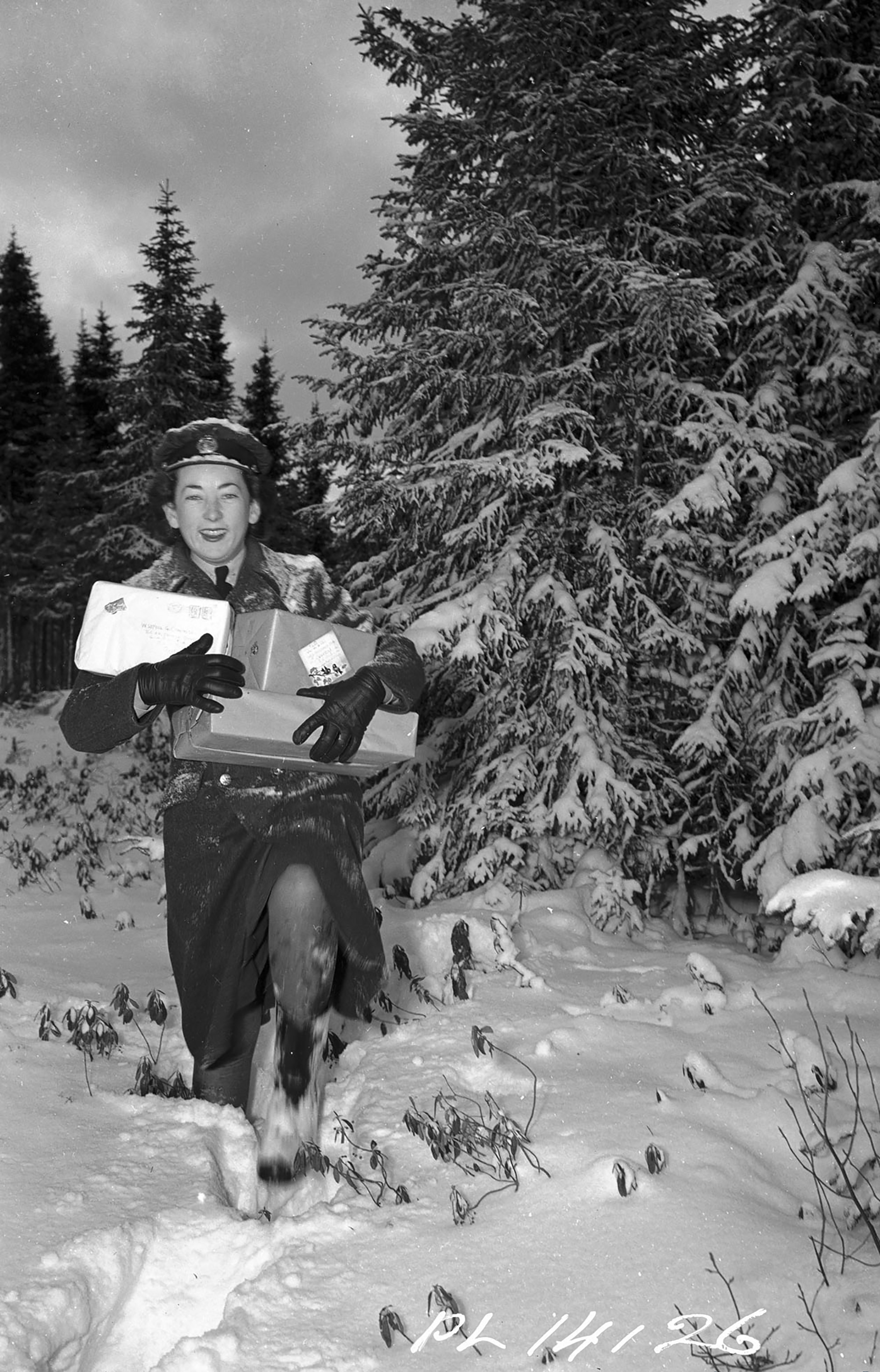 Leading Airwoman Gwen Cunnington (Burnaby, British Columbia) breaks a trail through 0.7 metres of Newfoundland snow as she takes a short-cut from the station post office to her RCAF outpost to deliver gifts on Christmas Eve, 1942.
