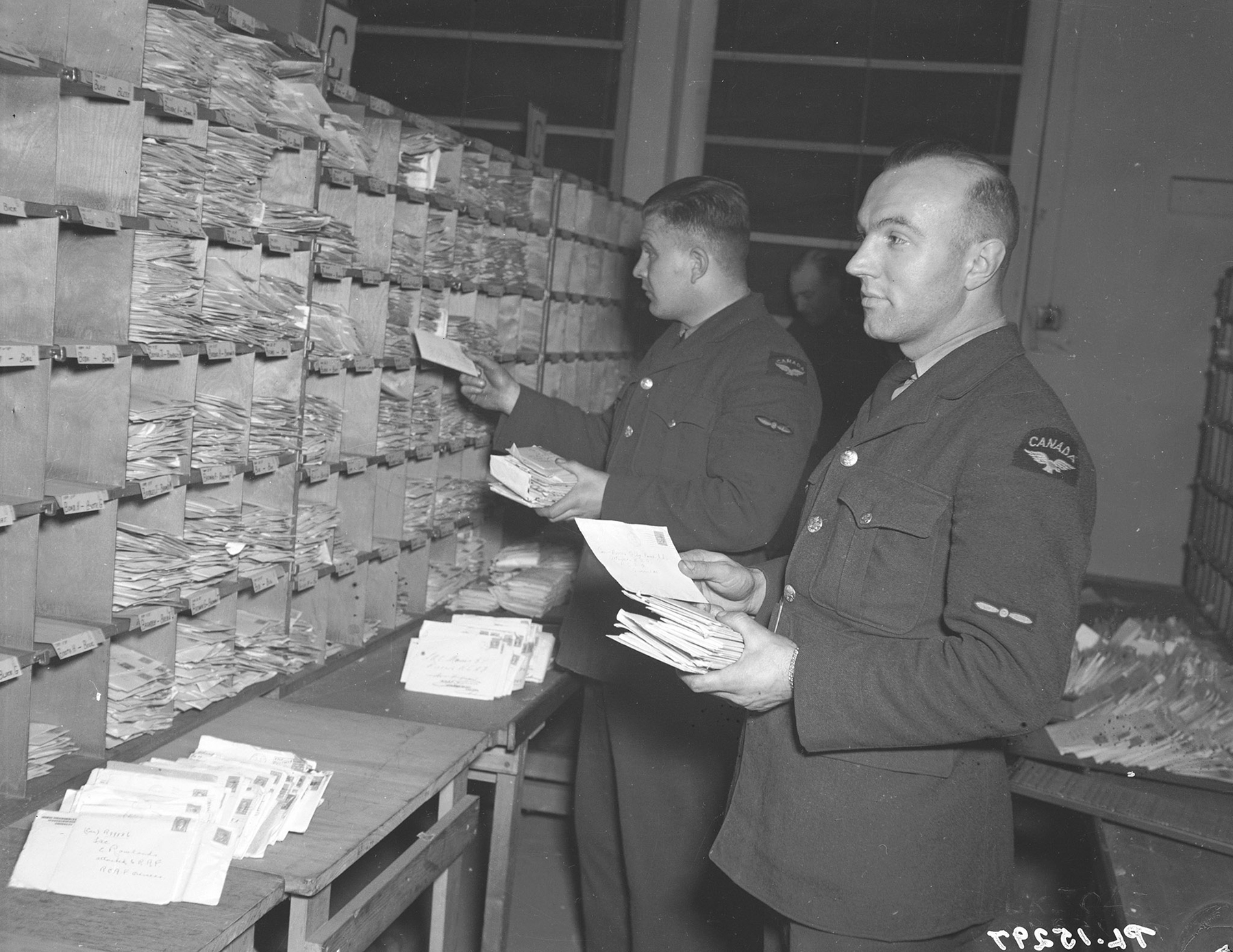 On January 14, 1943, Leading Aircraftman C.J. Doucet (Sydney, Nova Scotia) (front) and Leading Aircraftman G.A. Argue (Lemberg, Saskatchewan) sort letters alphabetically – many of them following their intended RCAF Overseas recipients from Royal Air Force station to station. PHOTO: DND Archives