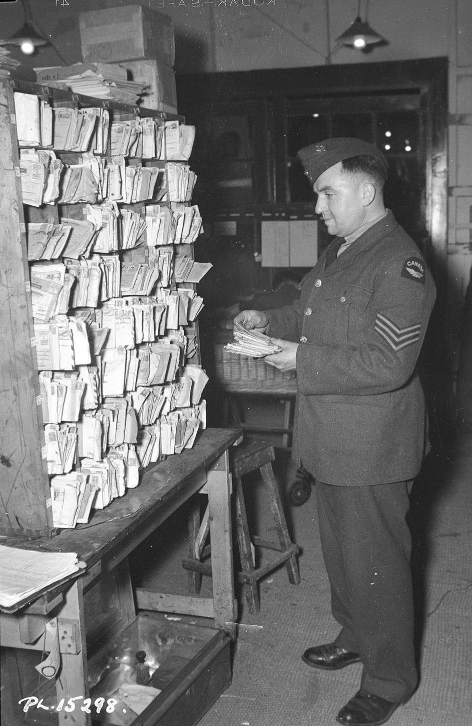 At the Base Post Office in the Midlands area of England, Sergeant Ray Meads (Toronto, Ontario) sorts misaddressed letters in alphabetical order by addressees' names. When a change-of-address card is received, he will make the change so that the letter can go out with as little additional delay as possible. PHOTO: DND Archives