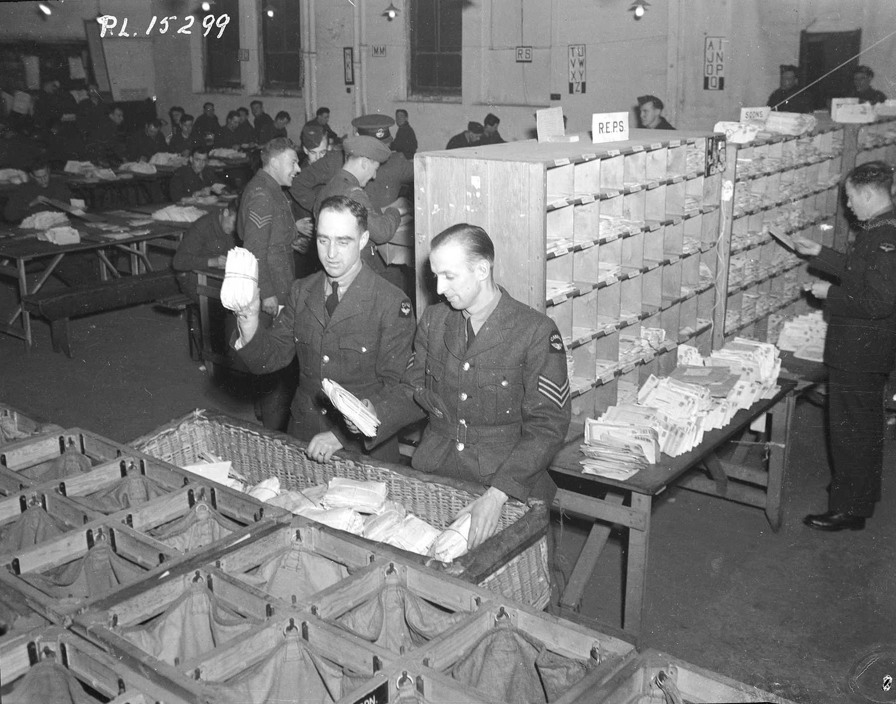 The mail in the foreground has been sorted by RCAF squadron or RAF station at the Base Post Office in the Midlands area of England. Leading Aircraftman A.D. Murray (left foreground) (Carman, Manitoba), and Sergeant W.J. Compton (Toronto Ontario) place bundles of sorted mail into the appropriate basket for transport to a squadron or station. PHOTO: DND Archives