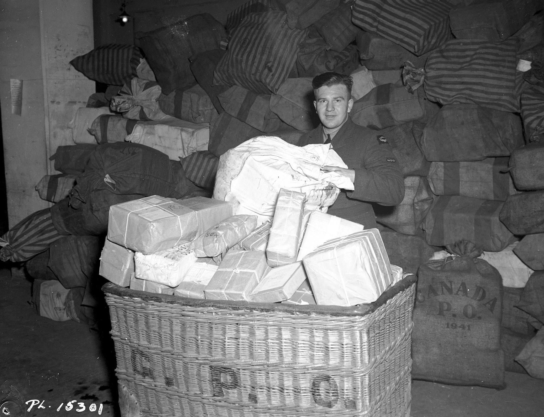 Leading Aircraftman G.A. Argue (Lemberg, Saskatchewan) empties parcel bags at the Base Post Office in the Midlands area of England on January 14, 1943. There will be a lot of happy members of the RCAF Overseas when this large shipment of mail is distributed. PHOTO: DND Archives