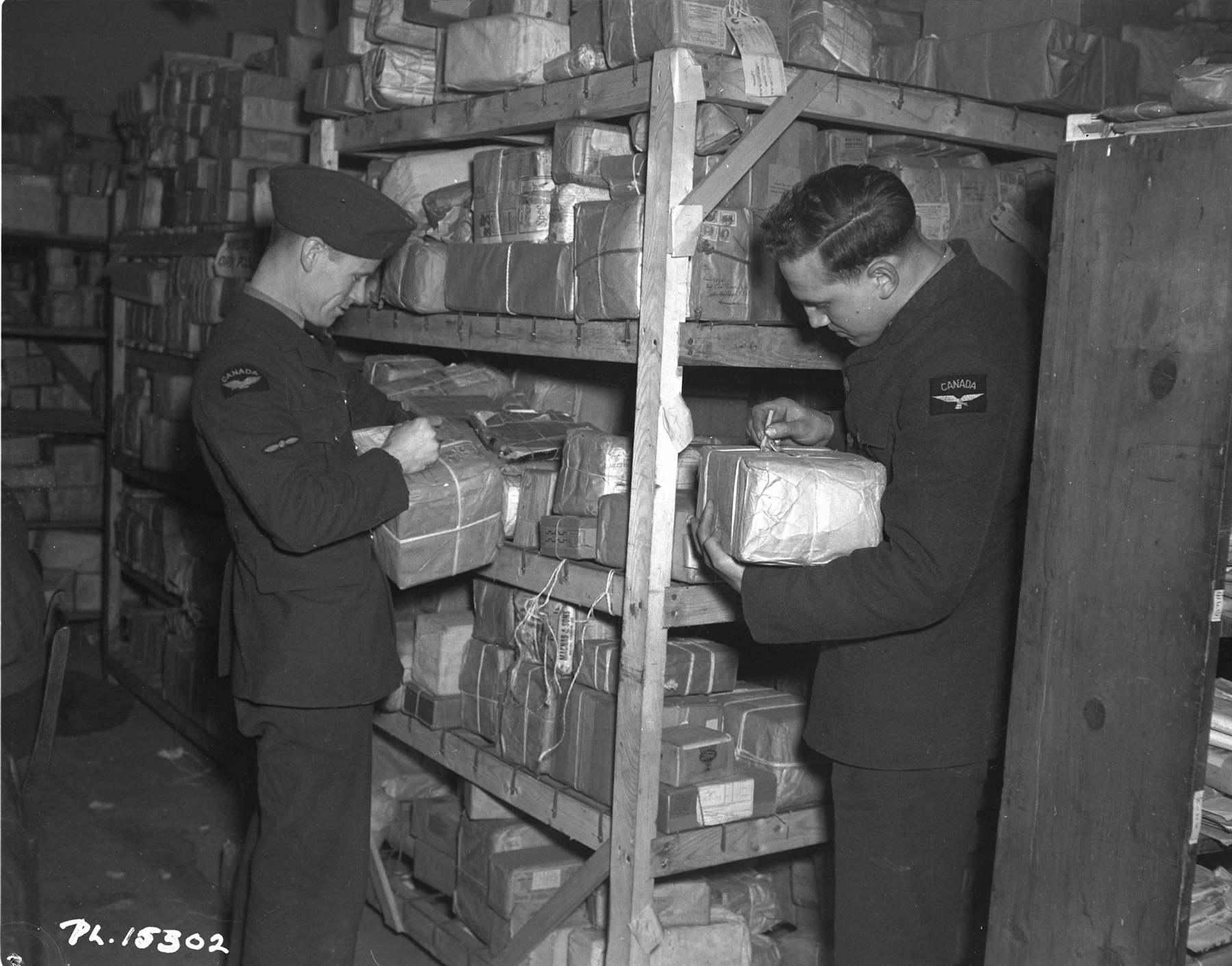 On January 14, 1943, Leading Aircraftman J.A. McGuire (left) and Aircraftman First Class F.R. Dane add two more misaddressed packages to the shelves at the Base Post Office in the Midlands area of England. This is what happens to packages when they are incorrectly addressed or when their intended recipients do not submit change-of-address cards: they are held until the correct address known. PHOTO: DND Archives