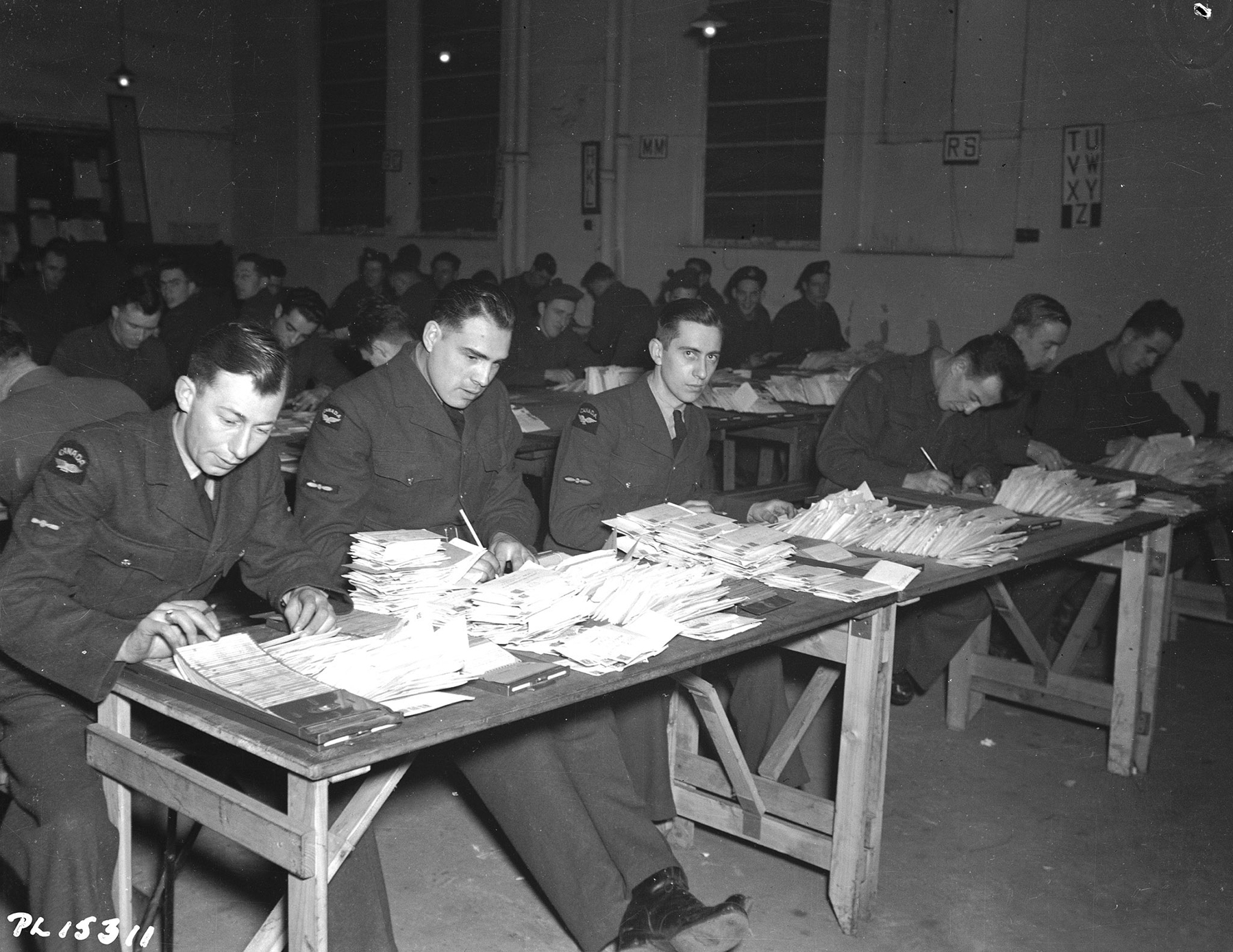 Members of the RCAF Postal Corps, including Leading Aircraftman R.V. Duguid (Montreal, Quebec), Leading Aircraftman J.N. Vandal (Winnipeg, Manitoba) and Leading Aircraftman J.S. Prescott (Toronto, Ontario), check the address of every letter to members of the RCAF Overseas. PHOTO: DND Archives