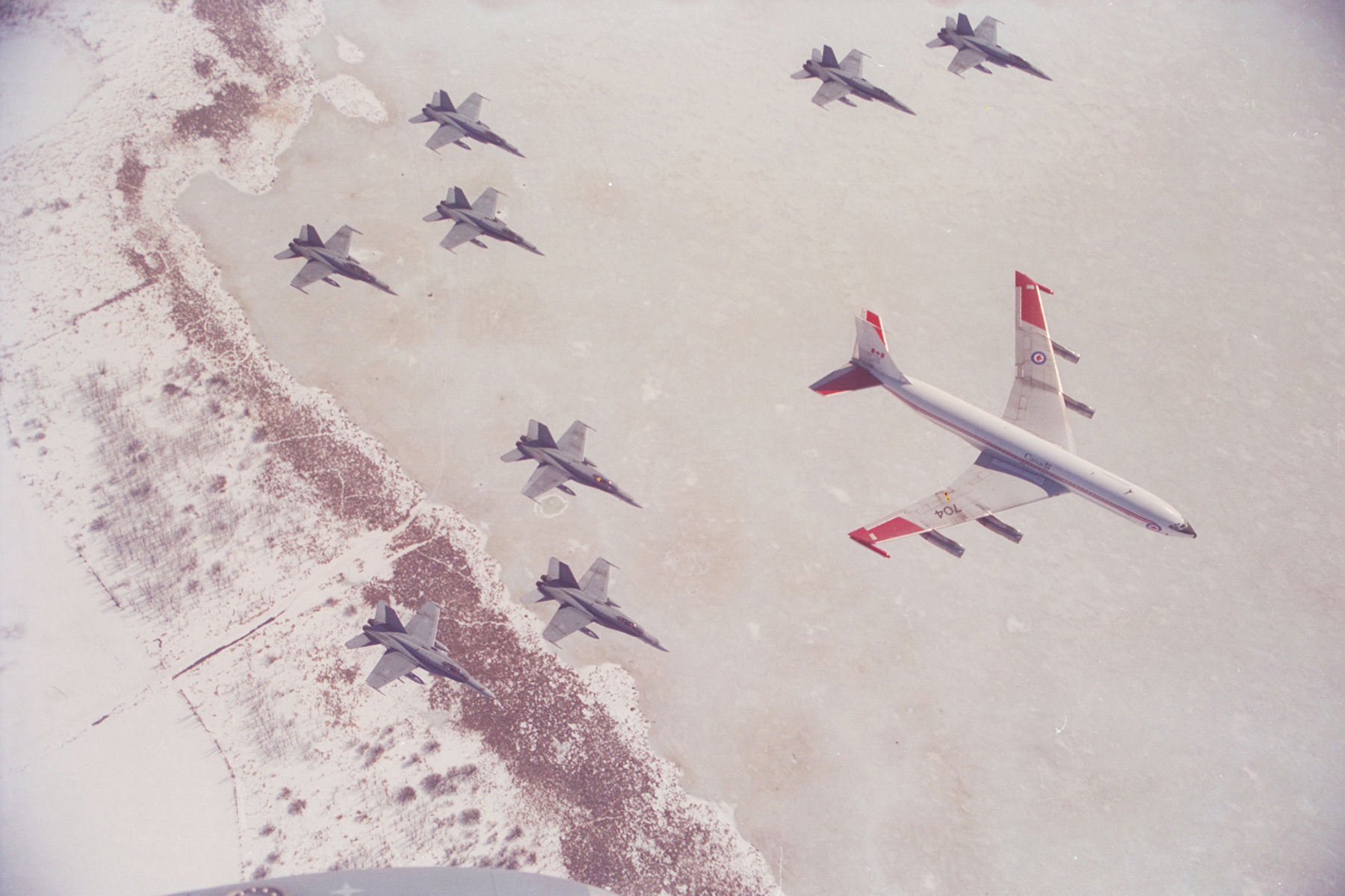 Upon their return from the first Gulf War (1990-1991), Canadian Armed Forces CF-188 Hornet fighters, led by a CC-137 (Boeing 707) aircraft transporting groundcrew and support personnel, approach downtown Ottawa, Ontario, over the bank of the frozen Ottawa River, in February 1991 to carry out a flyover marking their successful participation in Operation Desert Storm. PHOTO: Sergeant Norm Marion