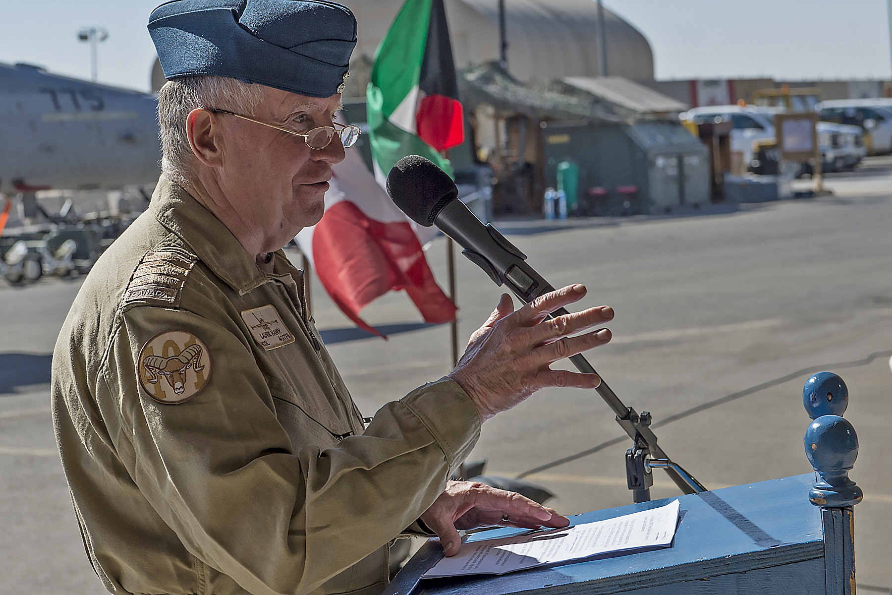 Honorary Colonel Laurie Hawn, the new honorary colonel of 401 Tactical Fighter Squadron, addresses squadron members deployed on Operation Impact in Kuwait, during his investiture ceremony on January 10, 2016.
