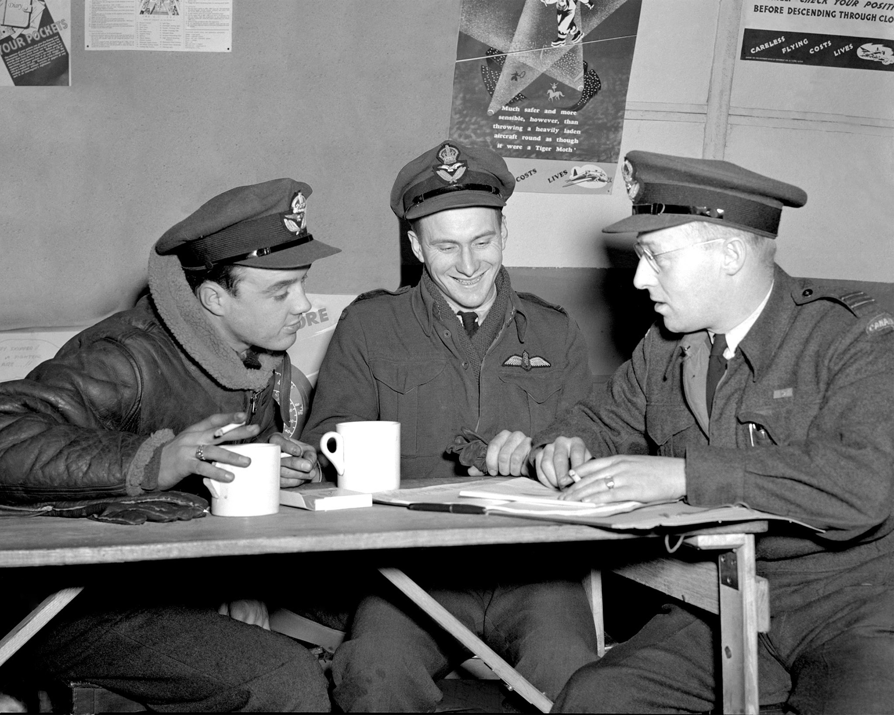 "Just after a successful raid on Dusiburg, Germany, signifying their full completion of a tour of operations, 408 ""Goose"" Squadron RCAF Overseas bomb aimer Pilot Officer R. Slessor (left) (Edmonton, Alberta) and Pilot Officer R.W. Bowhay, a pilot, (centre) (Three Hills, Alberta) undergo their final debriefing by station intelligence officer Flight Lieutenant W. Pilkington (Edmonton, Alberta). PHOTO: DND Archives"