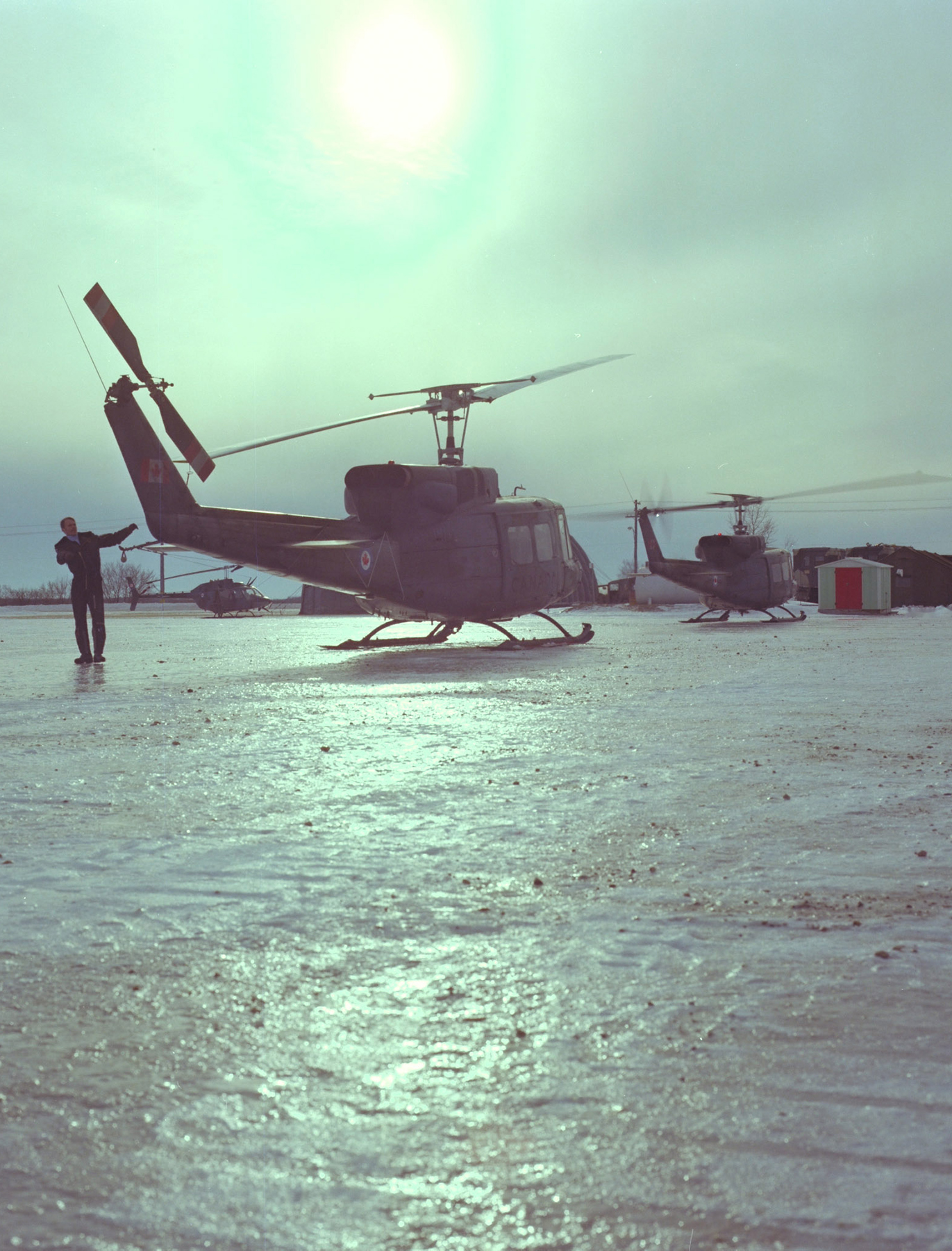 A 408 Squadron pilot does a pre-flight check on his Twin Huey helicopter on an icy day in 1981. PHOTO: Jack R. Seath