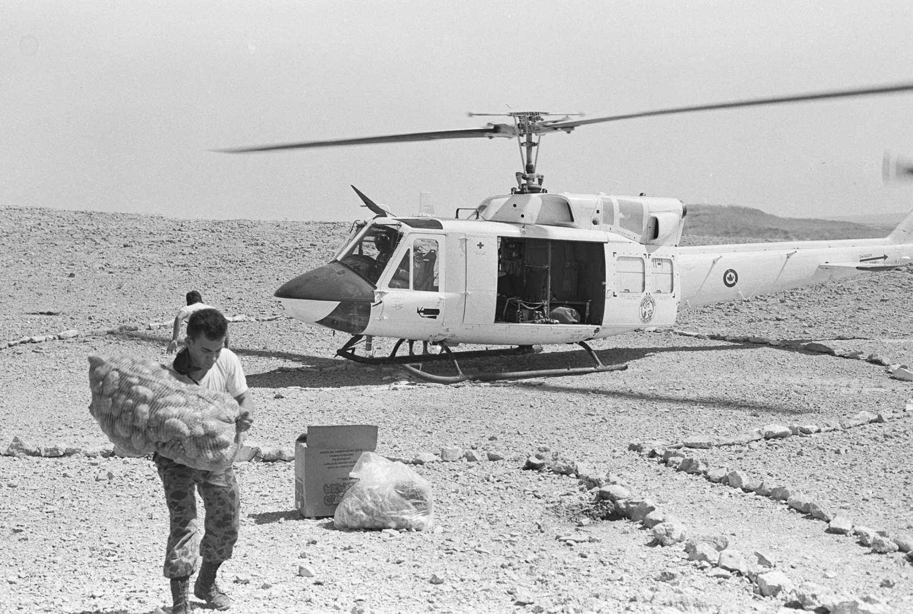 A Columbian soldier carries supplies delivered by a Royal Canadian Air Force 408 Squadron helicopter on Multinational Force and Observers duty in the Sinai Desert in 1986. PHOTO: Sergeant Tim Smith