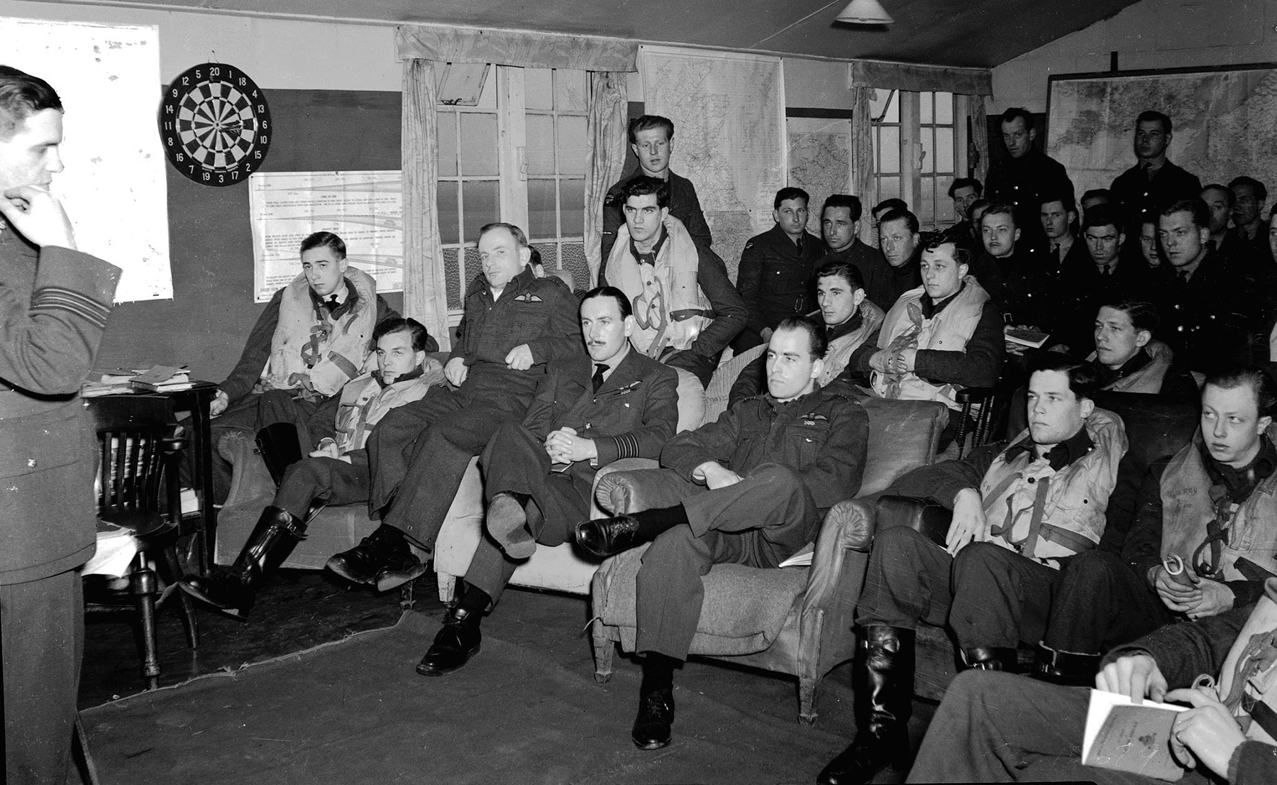 "At Royal Air Force Station Kenley in the United Kingdom on March 21, 1943, Squadron Leader F.K. Belton, also a Protestant padre, takes the church service in the dispersal hut of 403 Squadron, Royal Canadian Air Force. Each pilot is wearing his ""Mae West"", an inflatable life jacket, and all are ready to run to their aircraft in case an alarm should sound or they should be ordered on a sweep. Almost all of the aircrew are wearing battledress, as the squadron, commanded by Squadron Leader L.S. Ford, from Liverpool, Nova Scotia, is at readiness. 403 Squadron, formed on March 1, 1941, was the first RCAF 400-series squadron formed overseas as a direct result of Article XV of the British Commonwealth Air Training Plan. PHOTO: PL-15679, DND Archives"