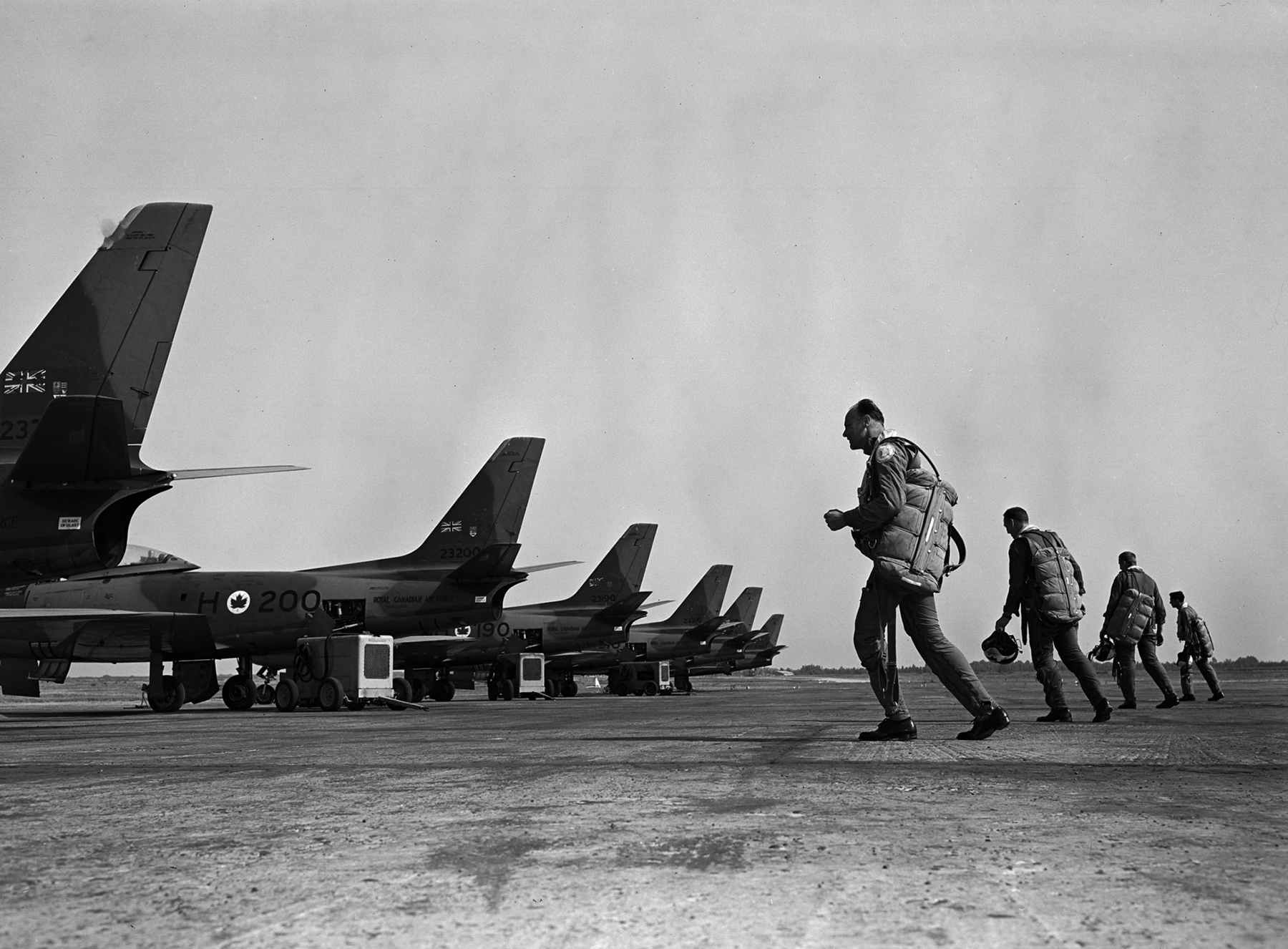 Pilots from 430 Squadron scramble for their F-86 Sabre jet aircraft during training at Rabat, Morocco, on August 29, 1955. PHOTO: PL-82680, DND Archives