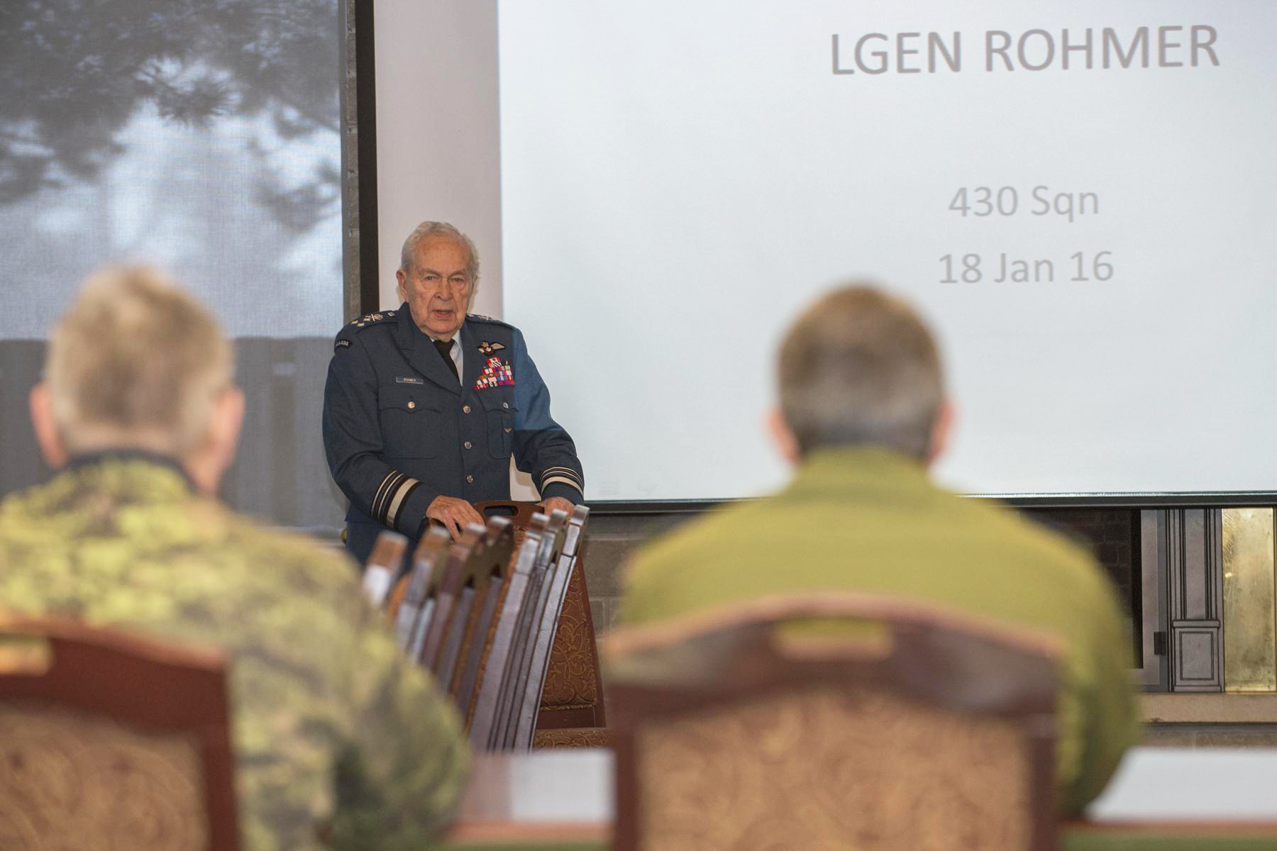 Squadron CWO Chief Warrant Officer Michel Trudel (left foreground) and commanding officer Lieutenant-Colonel Carol Potvin attend an historical briefing given by Second World War-era squadron member Lieutenant-General Richard Rohmer to members of the squadron.