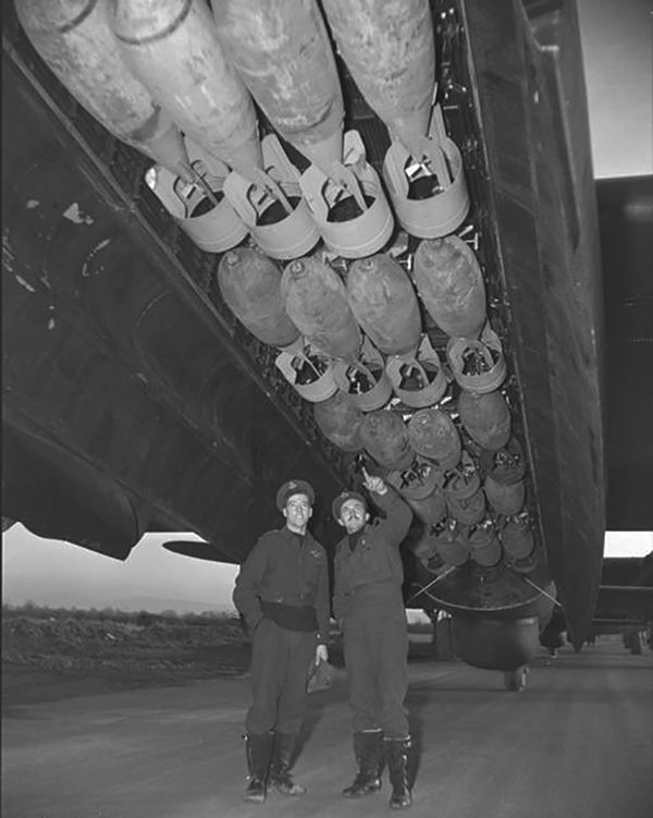 The enormous capacity of the Canadian-built Lancaster's bomb bay is well illustrated in this photograph. Both airmen are six-footers. They are Flying Officer Jack Carter, DFC, Ghost Squadron pilot of the RCAF Bomber Group in Britain, and his air bomber, Flying Officer W.C. Chester. They were preparing to take off for an operation against a synthetic oil refinery in the Ruhr, the last flight of their first tour. When the bomber stream returned after a successful attack, Flying Officer Carter's aircraft was the first to land at his airdrome, a flying courtesy traditionally extended to tour-finishers. PHOTO: DND Archives, PL-40683
