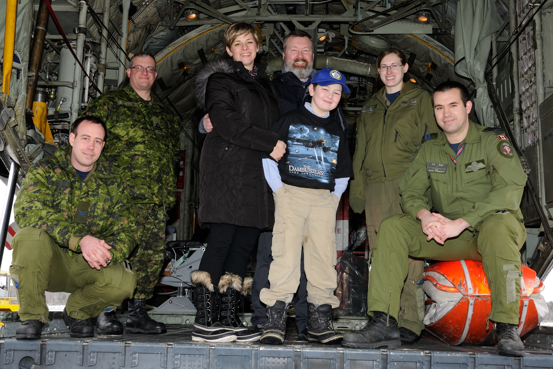 Loadmaster Corporal Christophe Rancourt (left), 14 Wing public affairs officer Lieutenant(N) Sylvain Rousseau, Anne-Marie McElrone, Michael MacDonald, Euan MacDonald, CC-130 Hercules pilot Captain Amanda Mattioli and Captain Derek Prescott, and air combat systems officer, gather for a photograph on March 11, 2016, when Euan MacDonald and his family spent the afternoon getting a look at what the modern Canadian Armed Forces do, particularly on Canada's East Coast. 413 Squadron personnel showed them through the CC-130 Hercules cargo aircraft and the CH-149 Cormorant helicopter used during search and rescue missions. PHOTO: Sergeant Peter Nicholson, GP2016-0055