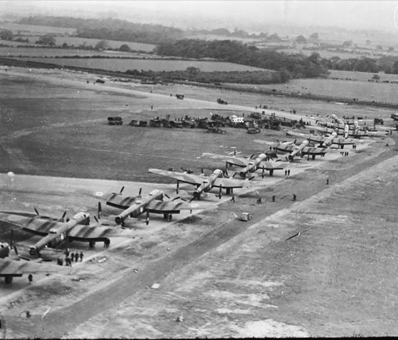 "An impressive aerial photograph of 12 Lancasters of RCAF Bomber Group ""Ghost"" Squadron lined up nose to tail taken May 31, 1945, the day they left for home. Fifteen Canadian-built Lancasters took off at one-minute intervals from their Bomber Station at Middleton St. George Yorks, the first of the Canadian squadrons to leave the United Kingdom since Victory in Europe Day. More will follow daily until all aircrew have gone. PHOTO: DND Archives, PL-44319"
