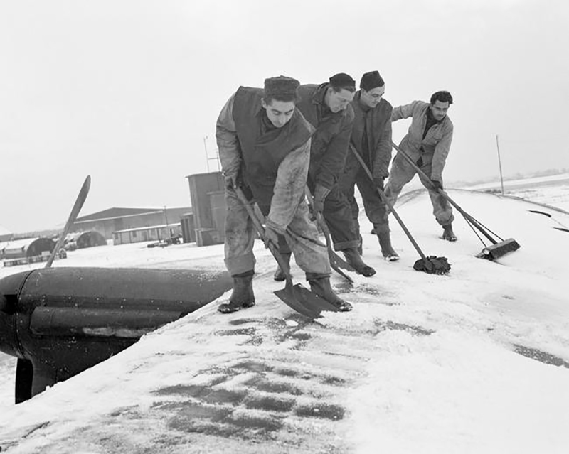 "Snow hits the station of No. 6 Bomber Group on January 11, 1945, where the ""Moose"" and ""Ghost"" squadrons are based, and that means a lot of work for all personnel, aircrew and groundcrew types alike. Up a-top the starboard wing of a Canadian-built Lancaster on the station, four of the boys scrape off the stubborn snow. They are Leading Aircraftman F.J. Chapioniere, a fitter from Champion, Alberta; Leading Aircraftman B. Holiday, from Elgin, Ontario; Leading Aircraftman J.G. Chagnon, from St. Hyacinthe, Quebec; and Leading Aircraftman W. Van Norman, from Guleph, Ontario. PHOTO: DND Archives, PL-41650"