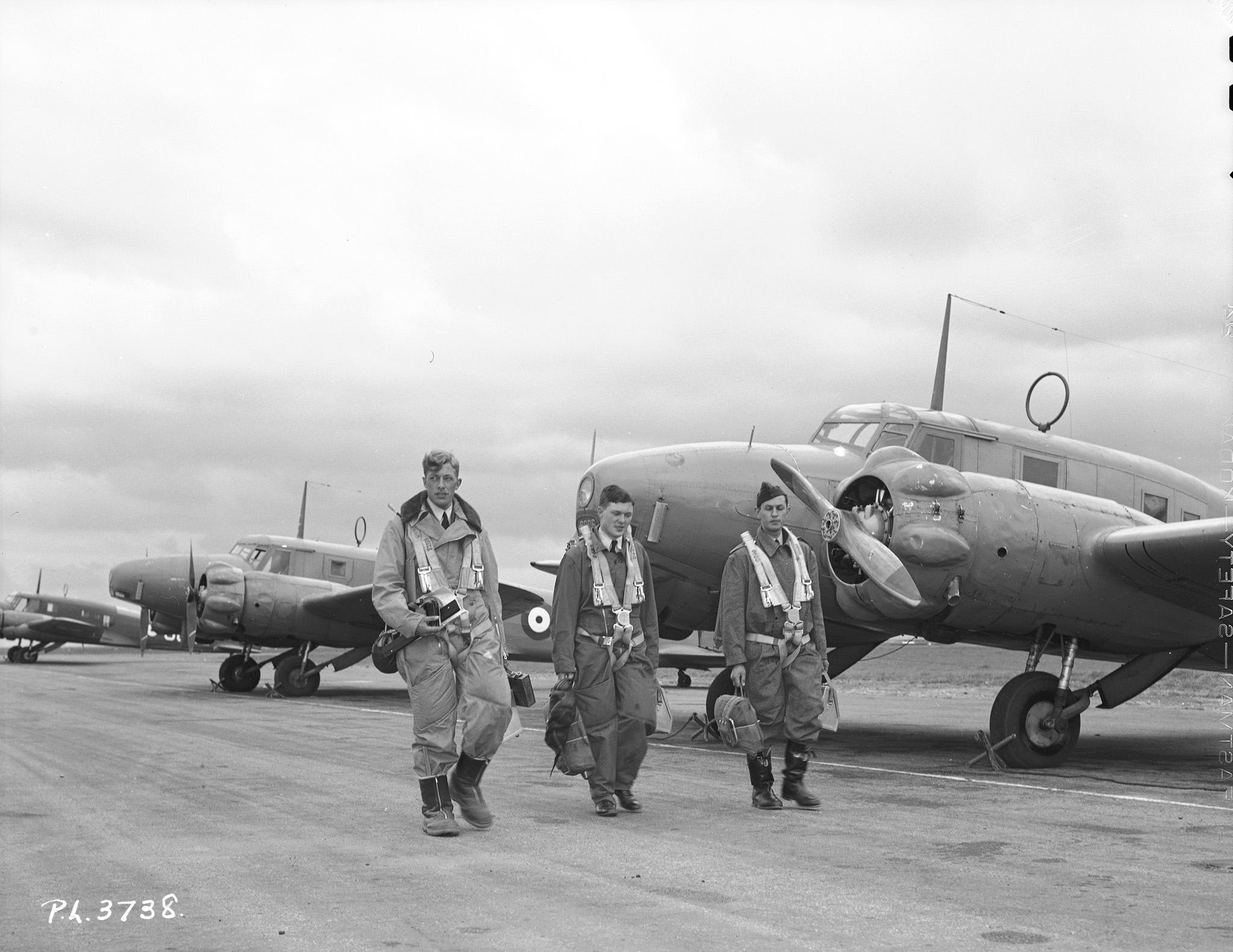 Three airmen walk down a line of Avro Ansons.