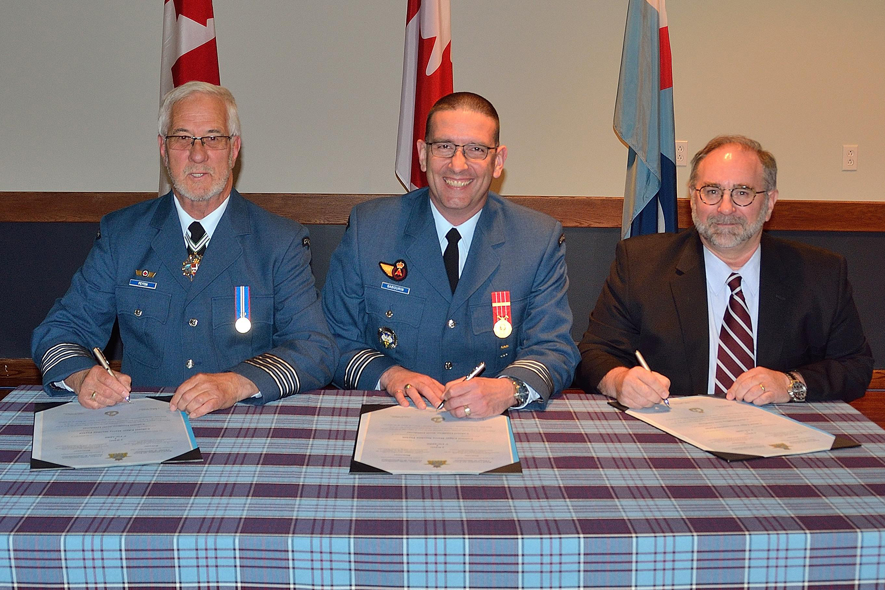 Lieutenant-Colonel Luc Sabourin (centre), wing commander of 5 Wing Goose Bay, Newfoundland and Labrador, presides over the investiture of award-winning photographer Geoff Goodyear (right) as honorary colonel of 5 Wing. He replaces outgoing Honorary Colonel Sterling Peyton.