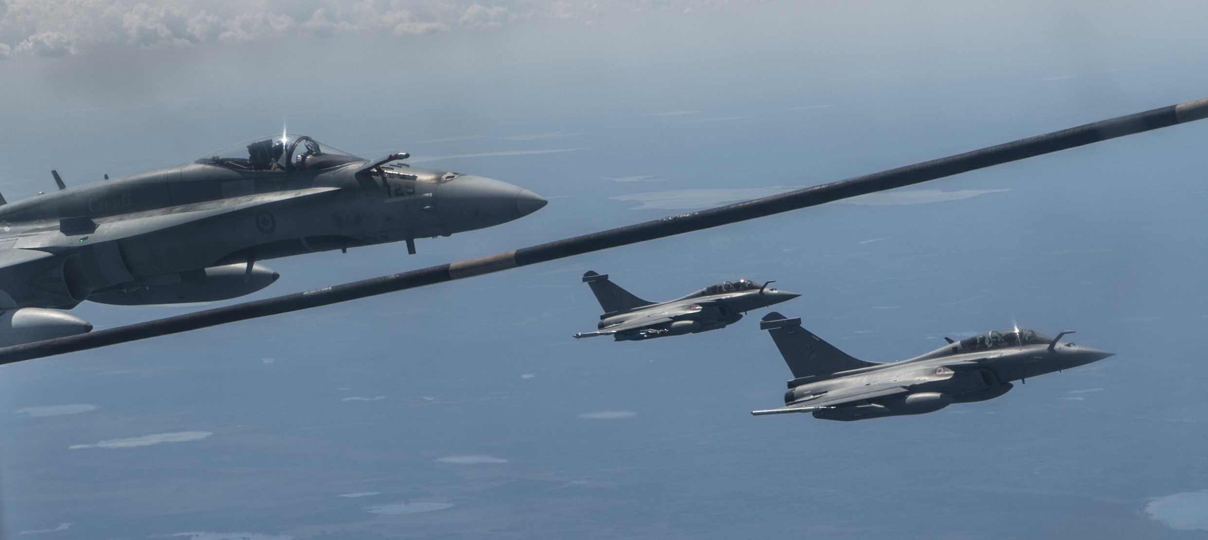 During Exercise Maple Flag, a CF-188 Hornet fighter aircraft (left) moves into position to refuel from a CC-130 Hercules aircraft over 4 Wing Cold Lake, Alberta, on June 21, 2016, while two French Air Force Rafale fighter aircraft fly alongside. PHOTO: Corporal Manuela Berger, CK01-2016-0510-214