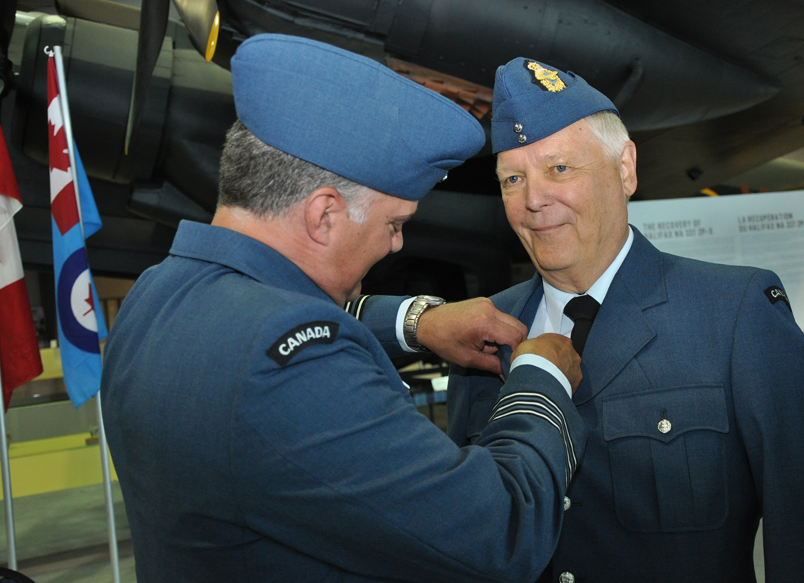 A man in an RCAF uniform pins a lapel pin on another man's uniform.