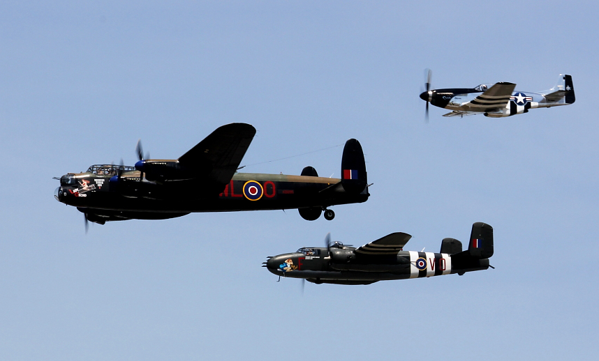 Three Second World War-era aircraft fly against the background of a clear blue sky.