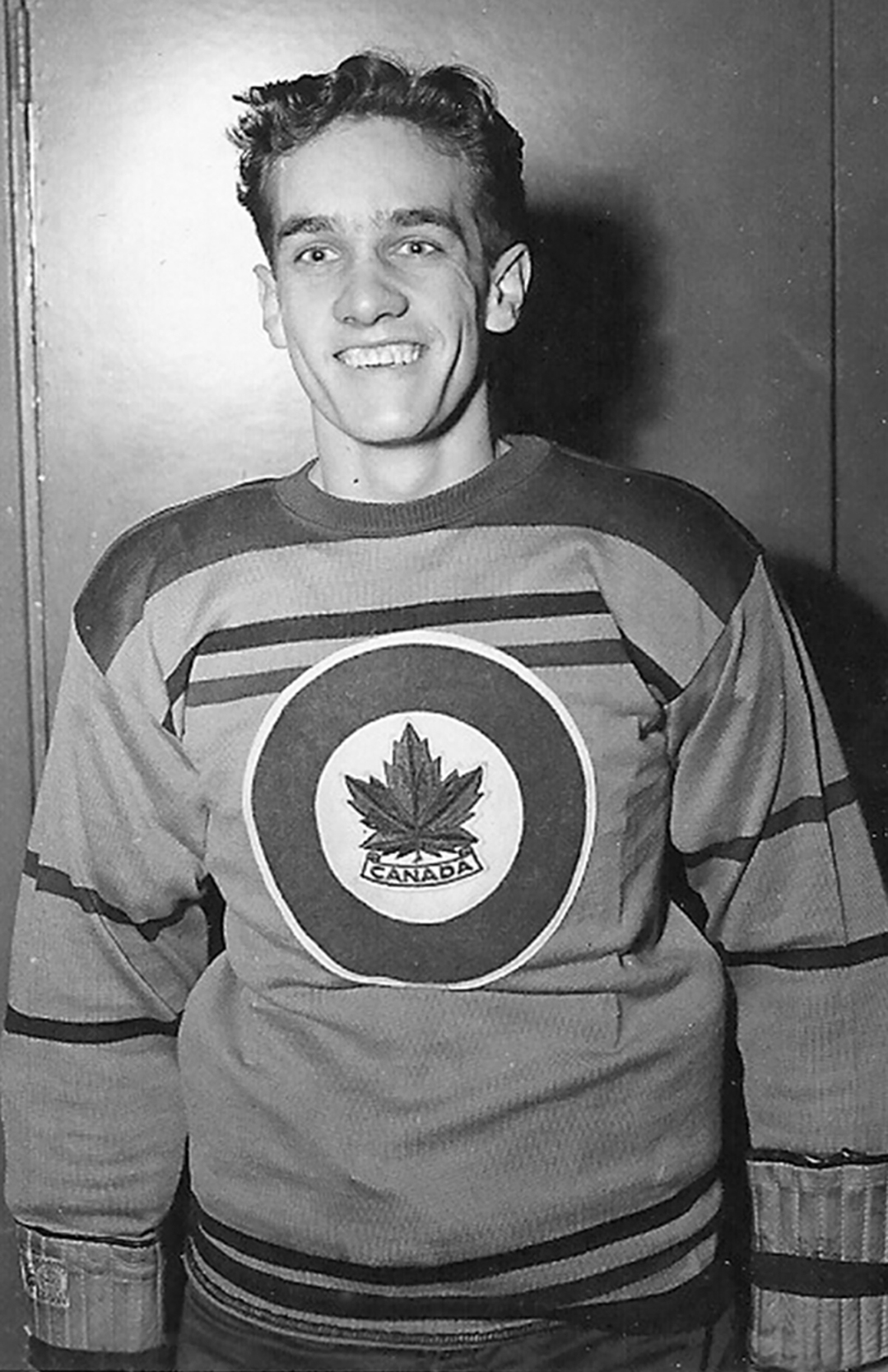 A hockey player in his uniform looks at the camera and grins.