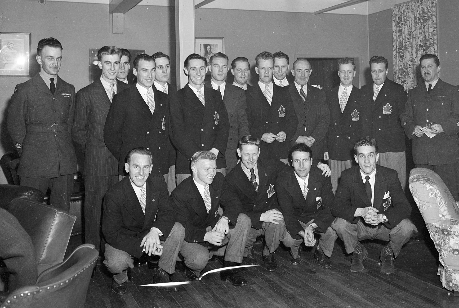 "The 1948 Olympic Champion RCAF Flyers gather for a photograph after receiving a tremendous ovation in the Sergeant's Mess at Ottawa's Beaver Barracks on April 8, 1948. Front row (left to right): Reg Schroeter, Orval Gravelle, Roy Forbes, Patsy Guzzo and Ted Hibberd. Back row (left to right): Warrant Officer Class 2 W.H. Fader, vice-president of the mess, Murray Dowey, Pete Lietchnitz, Hubert Brooks, Frank Dunster, Ab Renaud, George Mara, Louis LeCompte, Ross King, Sandy Watson, George ""Buck"" Boucher, Frank Boucher, Corporal George McFaul and Warrant Officer Class 2 Colin Campbell. Absent from the photo are André Laperrière and Wally Halder. PHOTO: DND Archves, PL-38853"