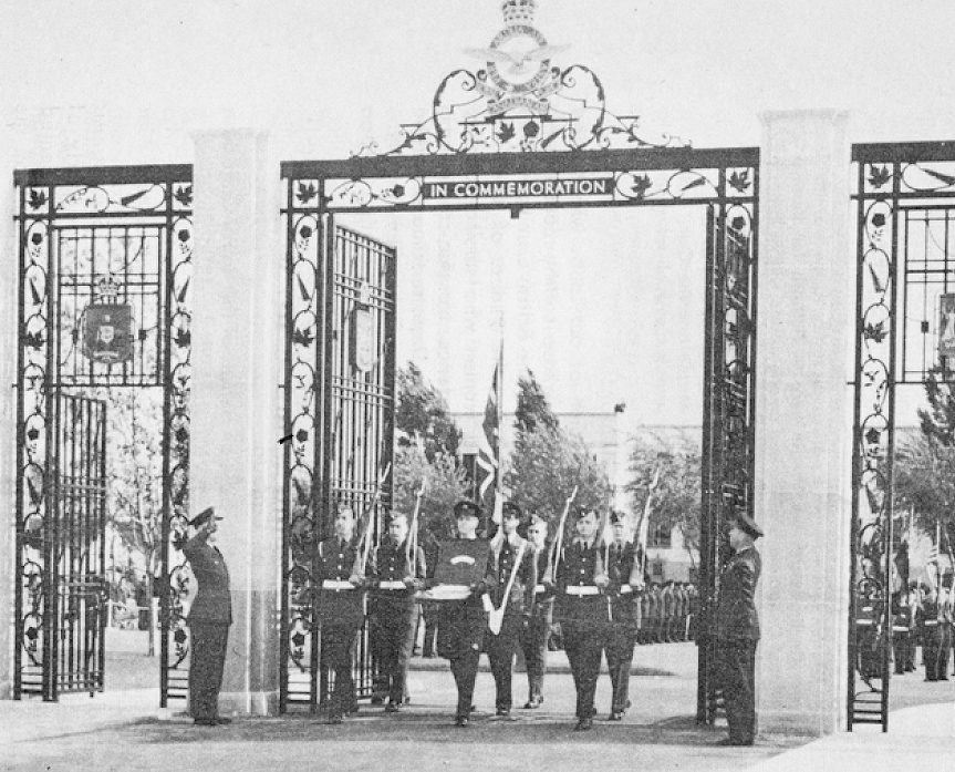 A group of military personnel walk through large gates