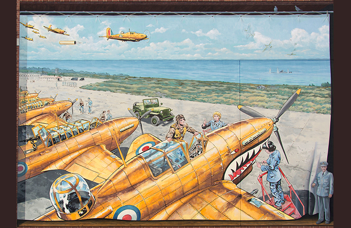 slide - In a painting, fighter aircraft, led by one towing a target drogue, head over a river, while others are serviced on an airfield.
