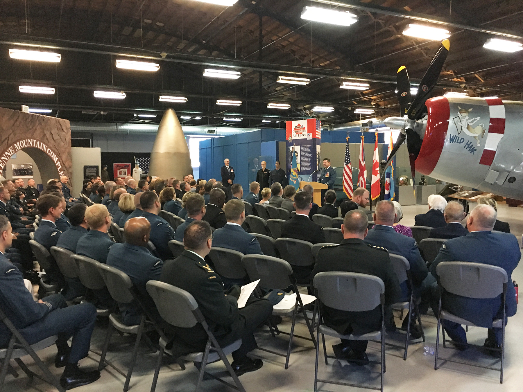"Lieutenant-General Pierre St-Amand, Deputy Commander North American Aerospace Defense Command (NORAD), addresses military members and their families during a September 18, 2016, ceremony held at the Peterson Air Force Base Museum in Colorado Springs, Colorado, to mark the 76th anniversary of the Battle of Britain. NORAD personnel from Canada and the United States, and military personnel from the United Kingdom, paid their respects. Squadron Leader (retired) George Sweanor, a Canadian who served in Great Britain with the Royal Canadian Air Force's 419 ""Moose"" Squadron in Bomber Command, also attended. Mr. Sweanor was a prisoner of war for 800 days in Stalag Luft III in Sagan, Poland, the ""Great Escape"" camp, during the war; after the war, he flew B-29 Superfortress Bombers when he was stationed with a United States Air Force/RCAF detachment in Edmonton, Alberta. PHOTO: Lieutenant(N) Marco Chouinard"