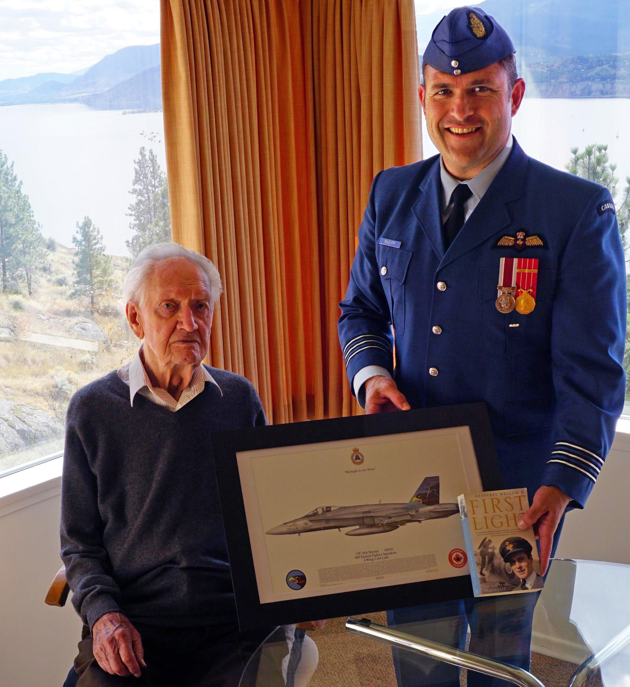 Lieutenant-Colonel William Radiff, commanding officer of 409 Squadron, presents Squadron Leader (retired) John Hart with a framed 409 Squadron commemorative print on the occasion of his 100th birthday. Squadron Leader John Hart presented Lieutenant-Colonel William Radiff a copy of the book First Light, written by Battle of Britain pilot Geoffrey Wellum, explaining that it is a very accurate description of what it was like to be a fighter pilot in the Second World War. PHOTO: Submitted