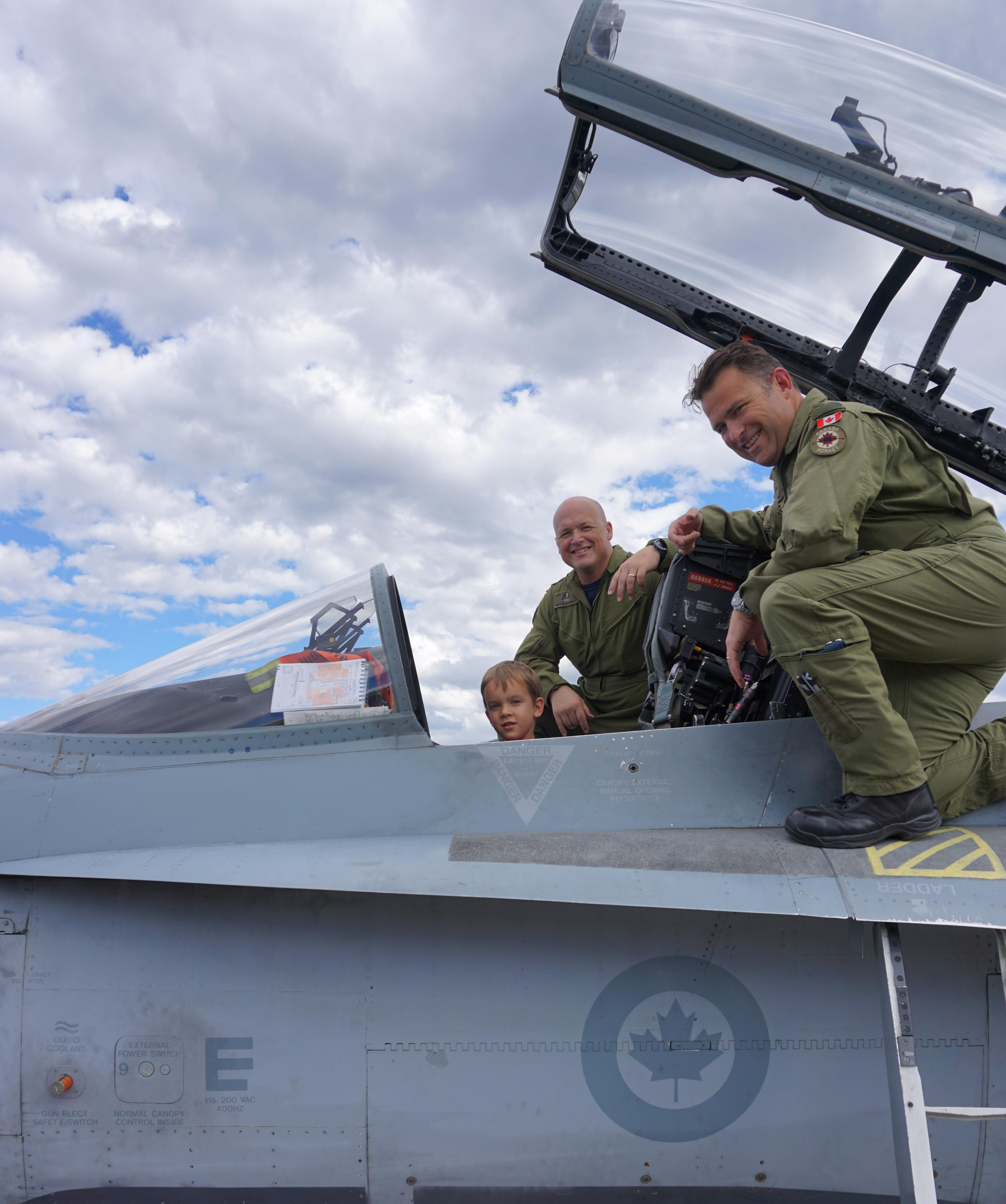 Squadron Leader (retired) John Hart's great-grandson Nathan sits in the cockpit of a CF-188 Hornet from 409 Tactical Fighter Squadron, located at 4 Wing Cold Lake, Alberta. With him are Major Denis Bandet and Lieutenant-Colonel William Radiff (right), both from 409 Squadron. The Hornets and their crews were in Penticton, British Columbia, to conduct a flyby over Squadron Leader Hart's home in honour of the veteran's 100th birthday and his service in the Battle of Britain. PHOTO: Submitted