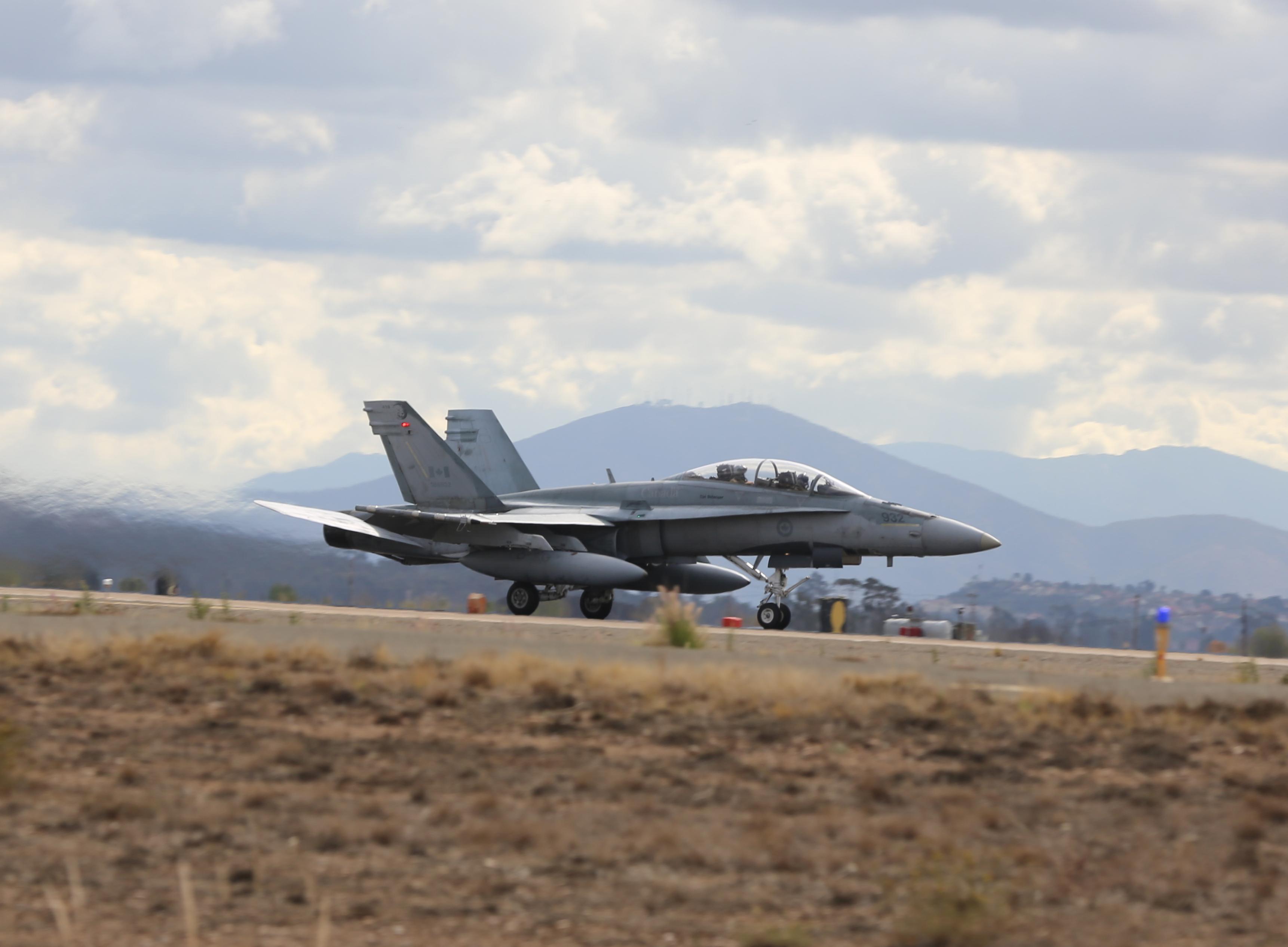 A CF-188 Hornet taxis on a runway in a desert.